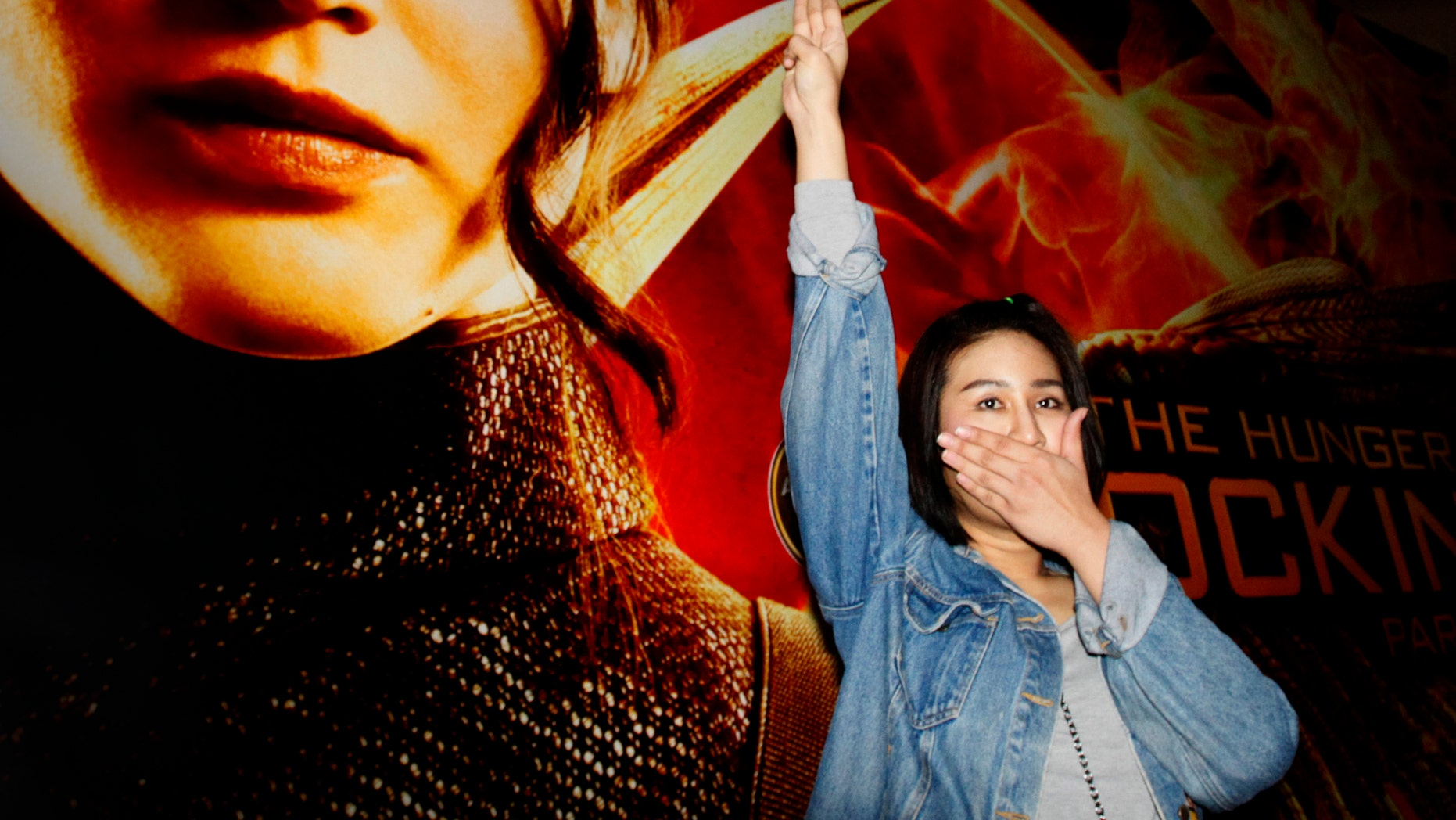 "Nov. 20, 2014: Nachacha Kongudom, 21, raises a three-finger salute outside a cinema where ""The Hunger Games: Mockingjay - Part 1"" is showing, in Bangkok, Thailand"