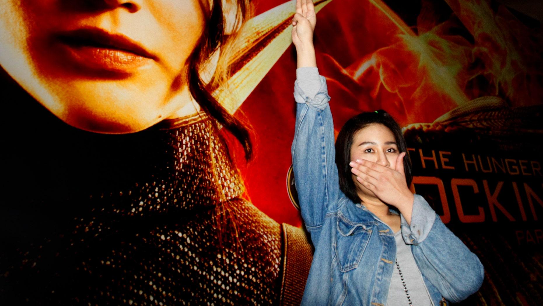 "Nov. 20, 2014: Nachacha Kongudom, 21, raises a three-finger salute outside a cinema where ""The Hunger Games: Mockingjay - Part 1"" is showing, in Bangkok, Thailand"