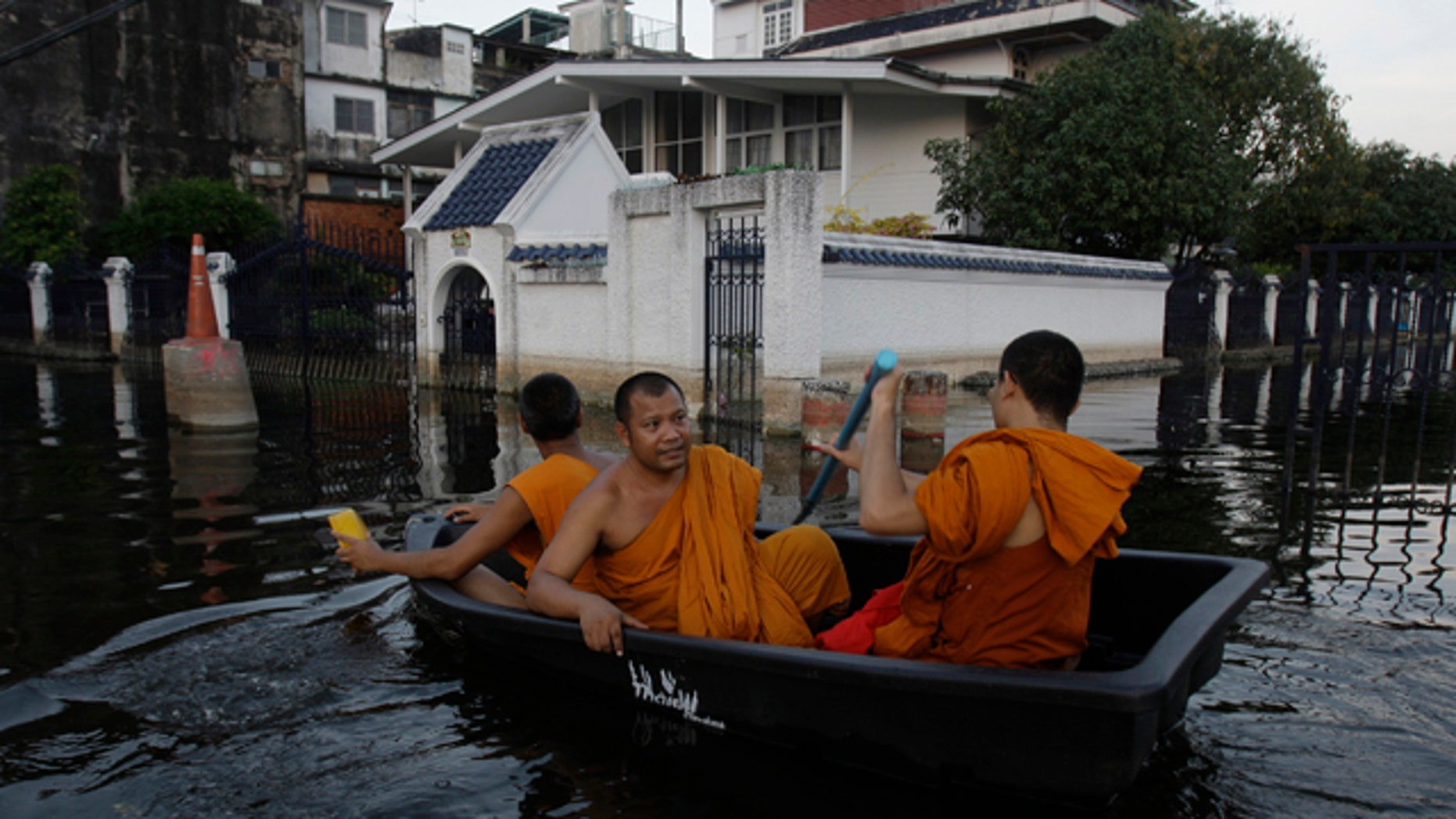 Nov. 6, 2011: Thai Buddhist monks navigate a small boat along flooded streets in Bangkok, Thailand.