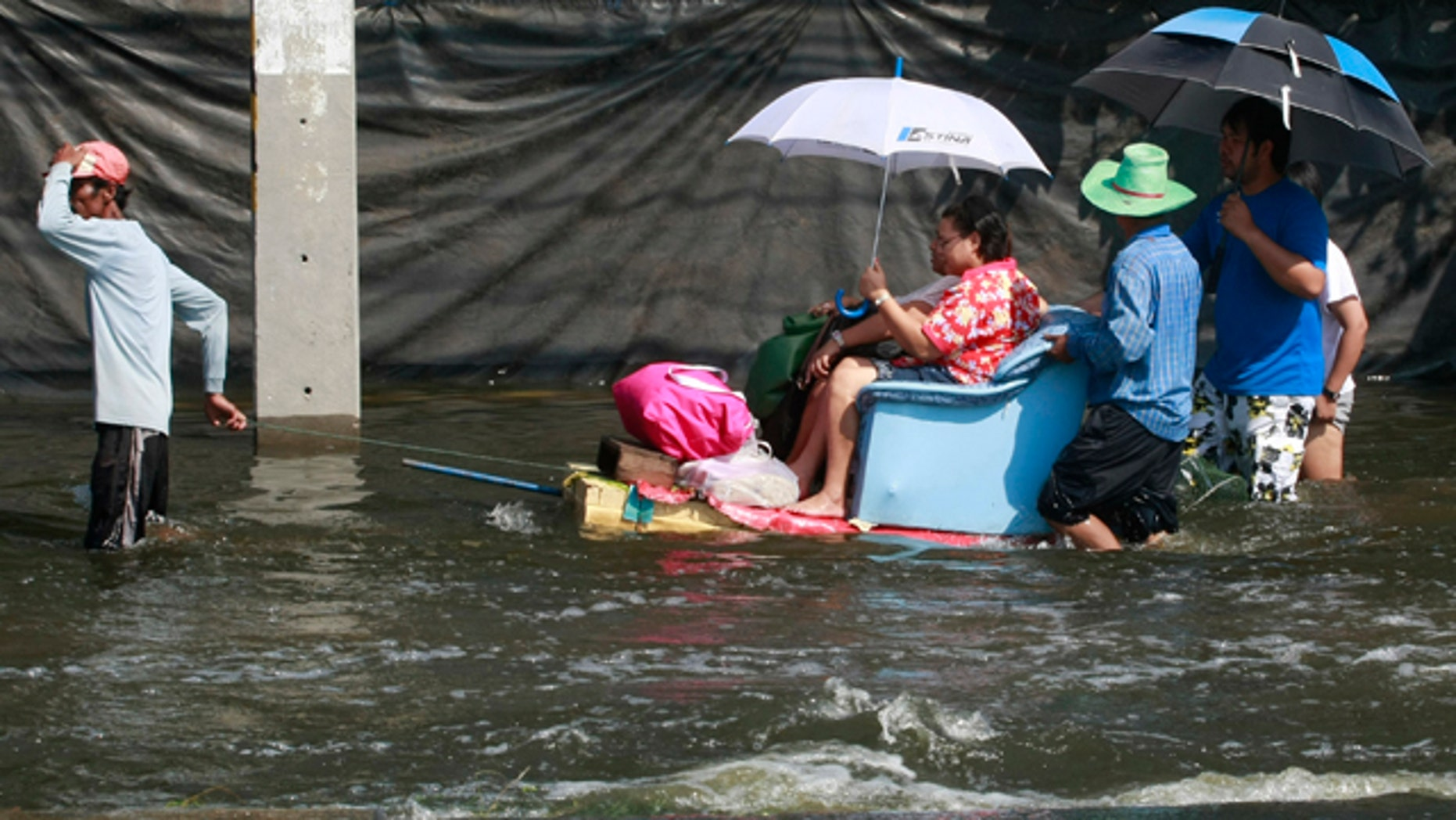 Oct. 24, 2011: A man pulls his decorated boat while making a service to his passenger on a flooded road in Bangkok, Thailand.