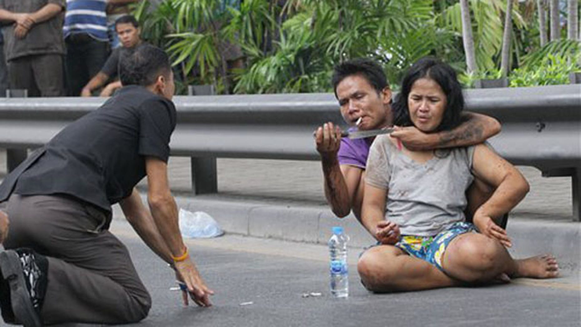 April 5, 2012: A Thai policeman talks to Sakdawut Hamsiri, 30, who holds a knife against his wife Thawee Naiyanit on a street in Bangkok.