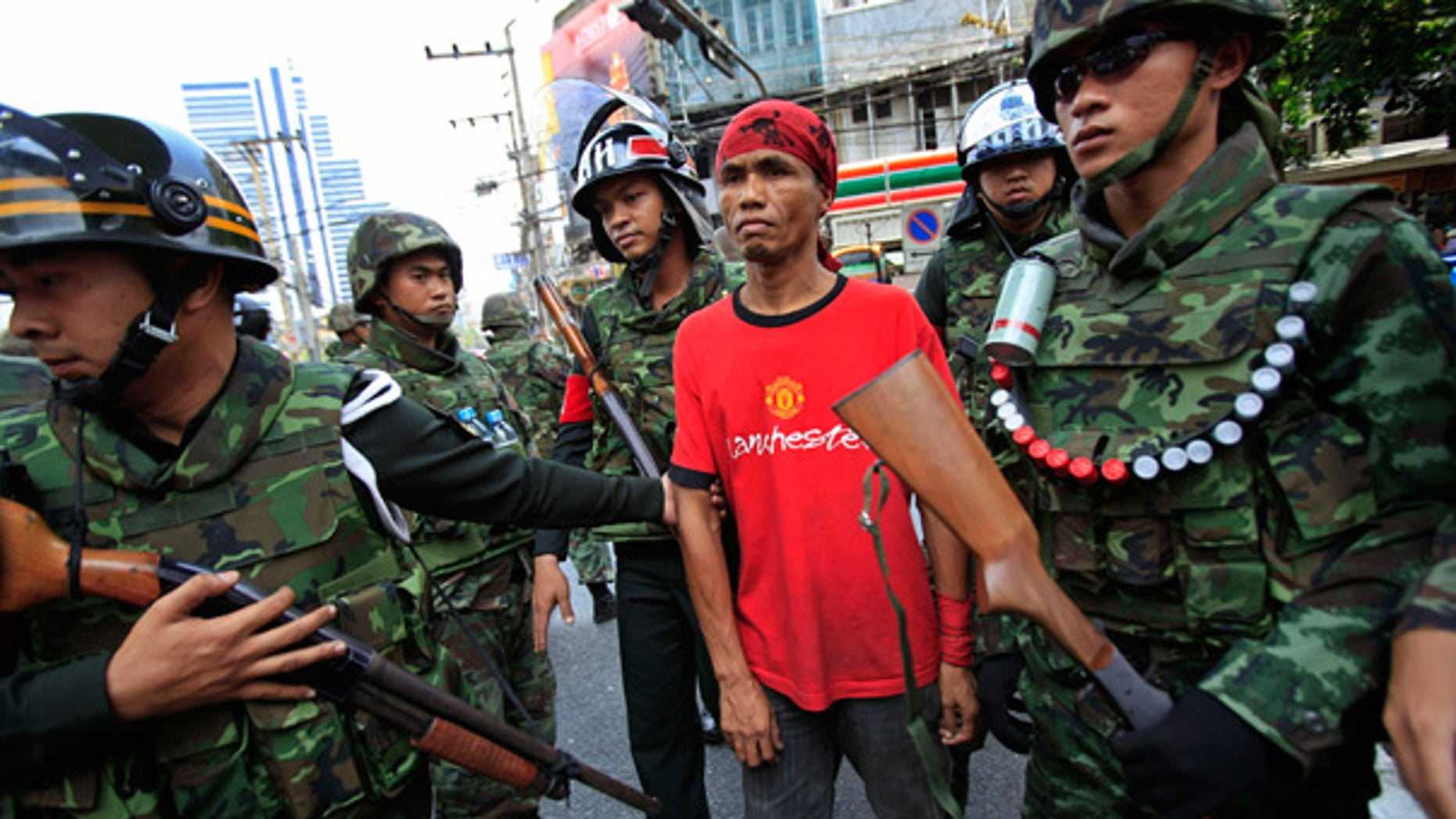 "April 25: A ""red shirt"" anti-government protester is detained by Thai soldiers near the residence of Thailand's prime minister in Bangkok."