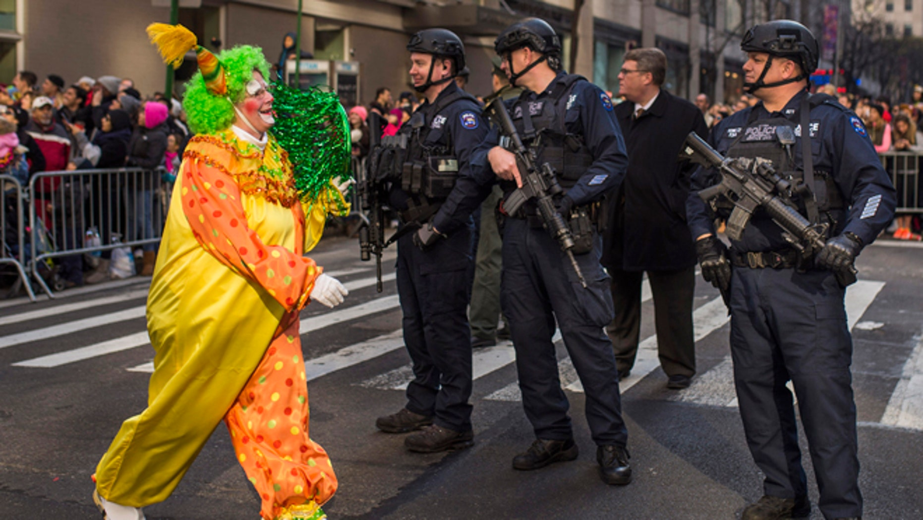 Nov. 26, 2015: A clown marches by heavily armed police stand guard during the Macy's Thanksgiving Day Parade in New York.