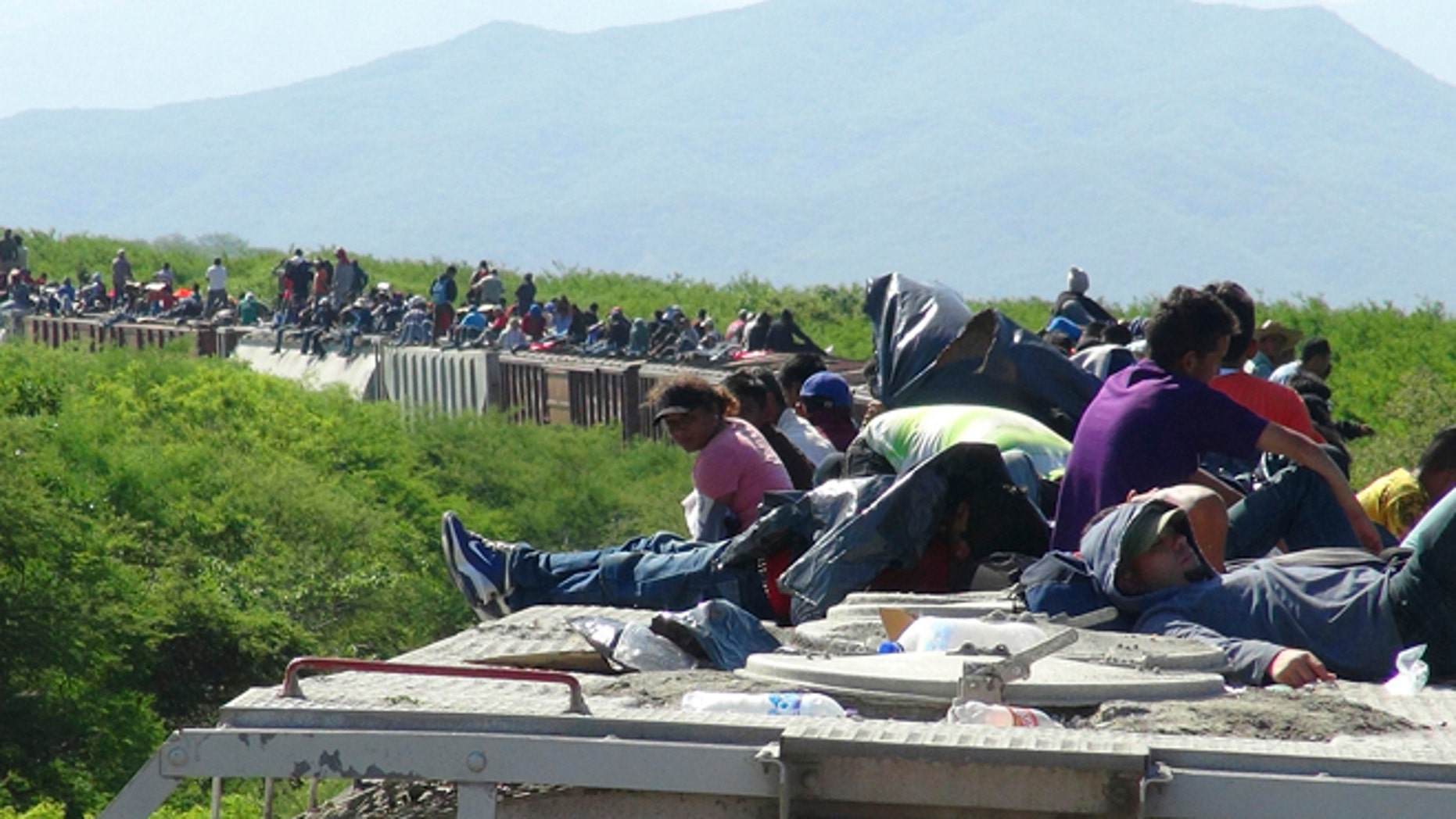 June 18, 2014: People hoping to reach the U.S. ride atop the wagon of a freight train, known as La Bestia (The Beast) in Ixtepec, in the Mexican state of Oaxaca. The train derailed on Wednesday, July 9, leaving about 1,300 migrants stranded, authorities said.