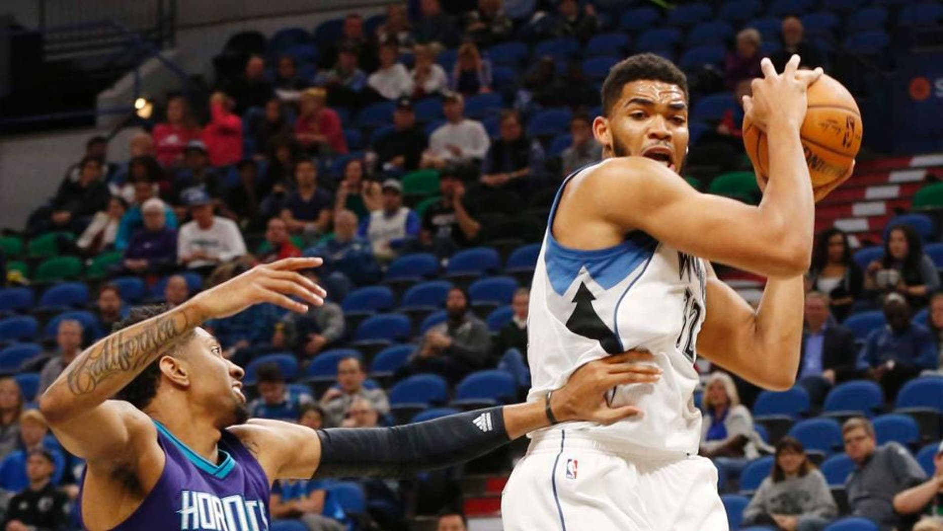 Minnesota Timberwolves' Karl-Anthony Towns, right, out jumps Charlotte Hornets' Christian Wood for a rebound in the first quarter of an NBA preseason basketball game Friday, Oct. 21, 2016, in Minneapolis. (AP Photo/Jim Mone)