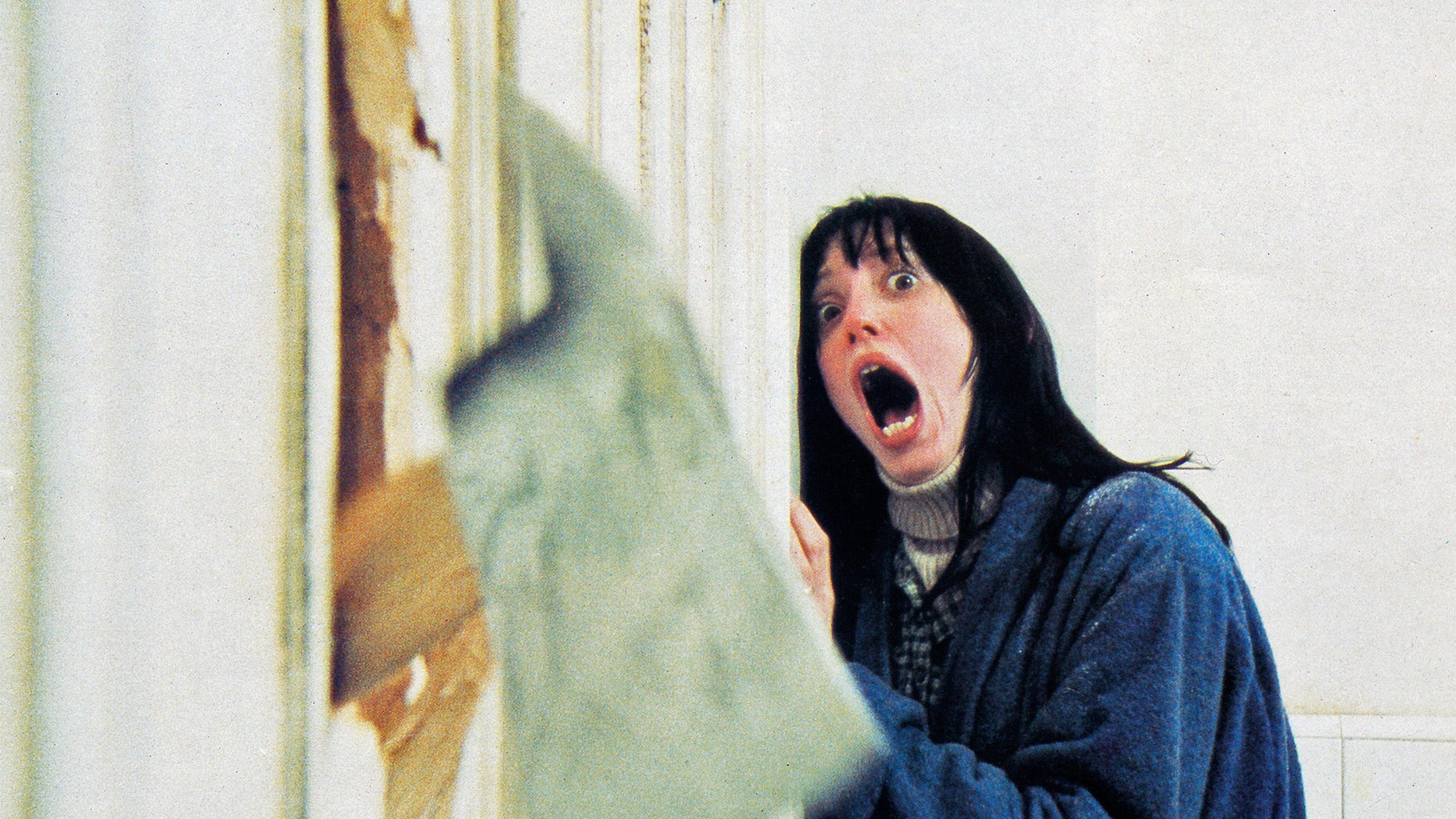 actress Shelley Duvall, recoils in shock as her husband chops through the bathroom door with a fire axe in a scene from 'The Shining', directed by Stanley Kubrick