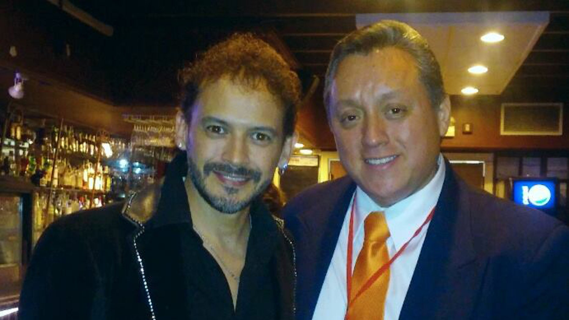 """In this March 13, 2016 photo released by Miguel Angel Sanchez on June 19, 2016, Sanchez, right, stands with Mexican singer Alejandro """"Jano"""" Fuentes in a restaurat in Chicago. Fuentes, who appeared on the Mexican version of """"The Voice"""" in 2011 was shot and critically wounded on June 18 in an ambush shortly after celebrating his birthday with friends in Chicago. (Miguel Angel Sanchez via AP)"""