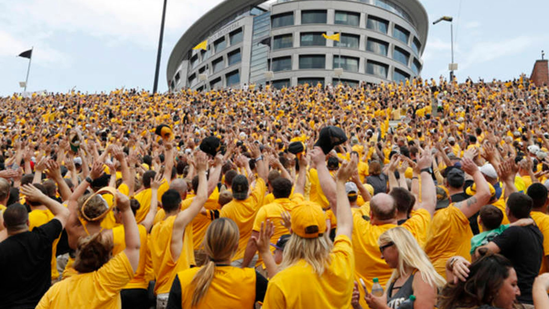 Iowa fans wave to children in the University of Iowa Stead Family Children's Hospital at the end of the first quarter of an NCAA college football game against North Texas, Saturday, Sept. 16, 2017,