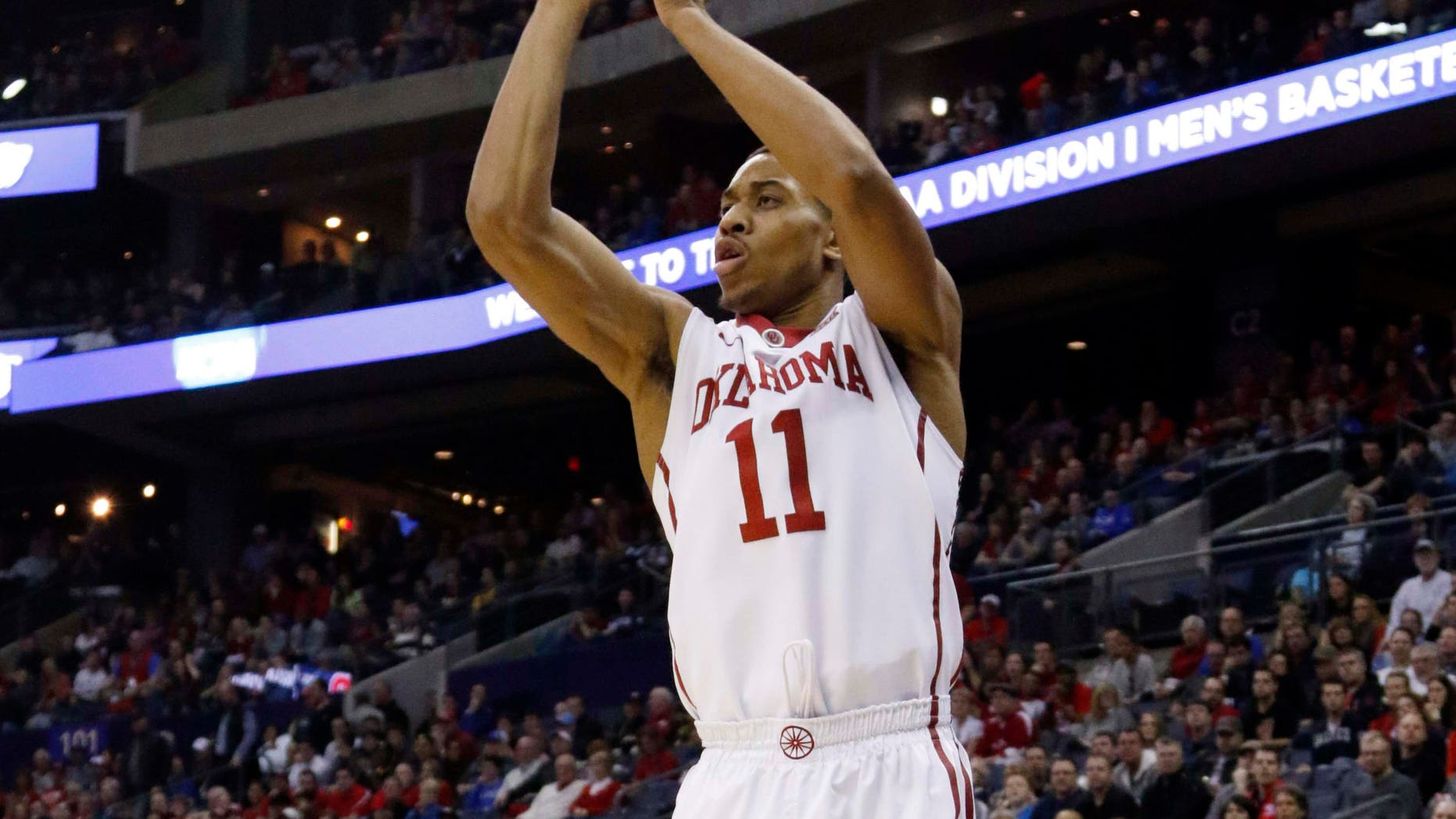 March 22, 2015: Oklahoma's Isaiah Cousins shoots a 3-point shot against Dayton in the first half of an NCAA tournament college basketball game in the Round of 32 in Columbus, Ohio.