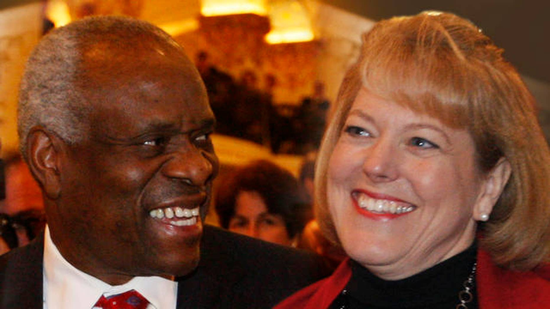 FILE: In this Nov. 15, 2007, photo, Supreme Court Justice Clarence Thomas, left, sits with his wife Virginia Thomas, as he is introduced at the Federalist Society in Washington.
