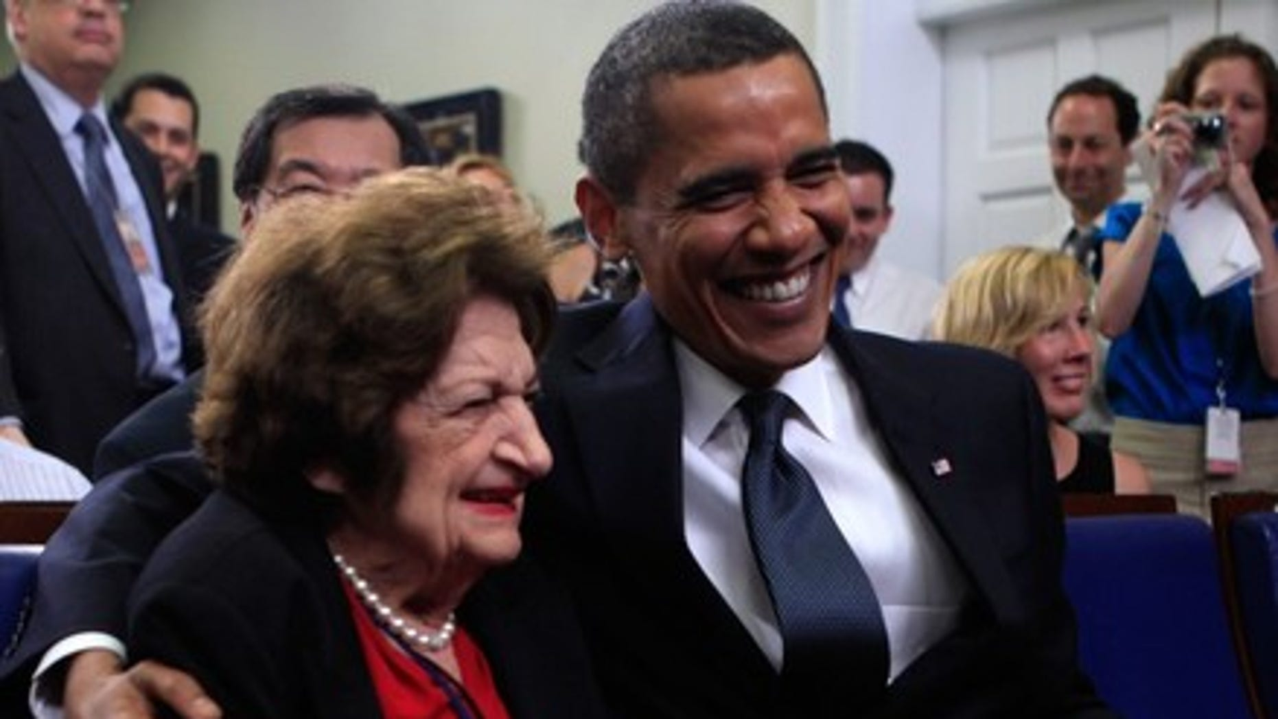 Aug. 4, 2009: President Obama mugs for the camera with Hearst White House columnist Helen Thomas during a mutual birthday celebration in the White House briefing room. (Reuters)