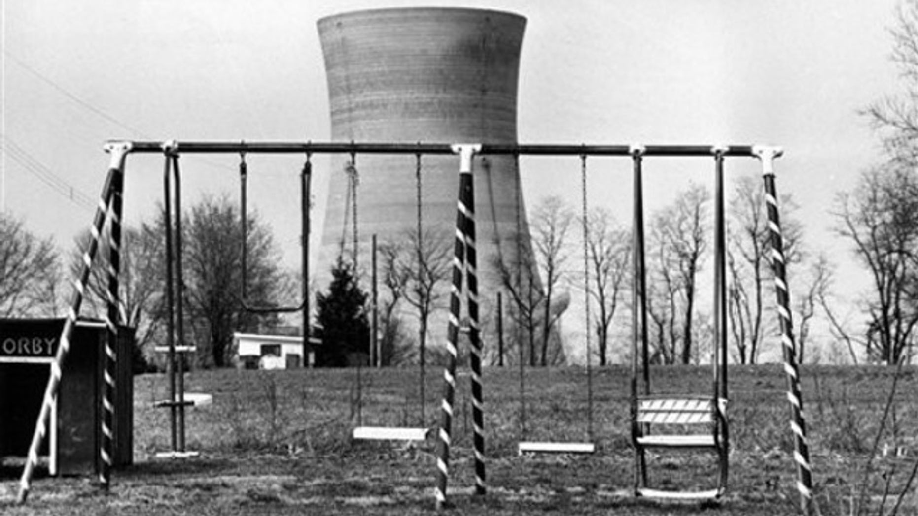 This file photo from March 30, 1979 shows a cooling tower of the Three Mile Island nuclear power plant near Harrisburg, Pa. , as it looms behind an abandoned playground. The partial meltdown at Three Mile Island nuclear plant in 1979 routed more than 180,000 people living within 50 miles of the plant, a five-day evacuation nightmare that residents are reliving as the nuclear plant crisis unfolds in Japan (AP).