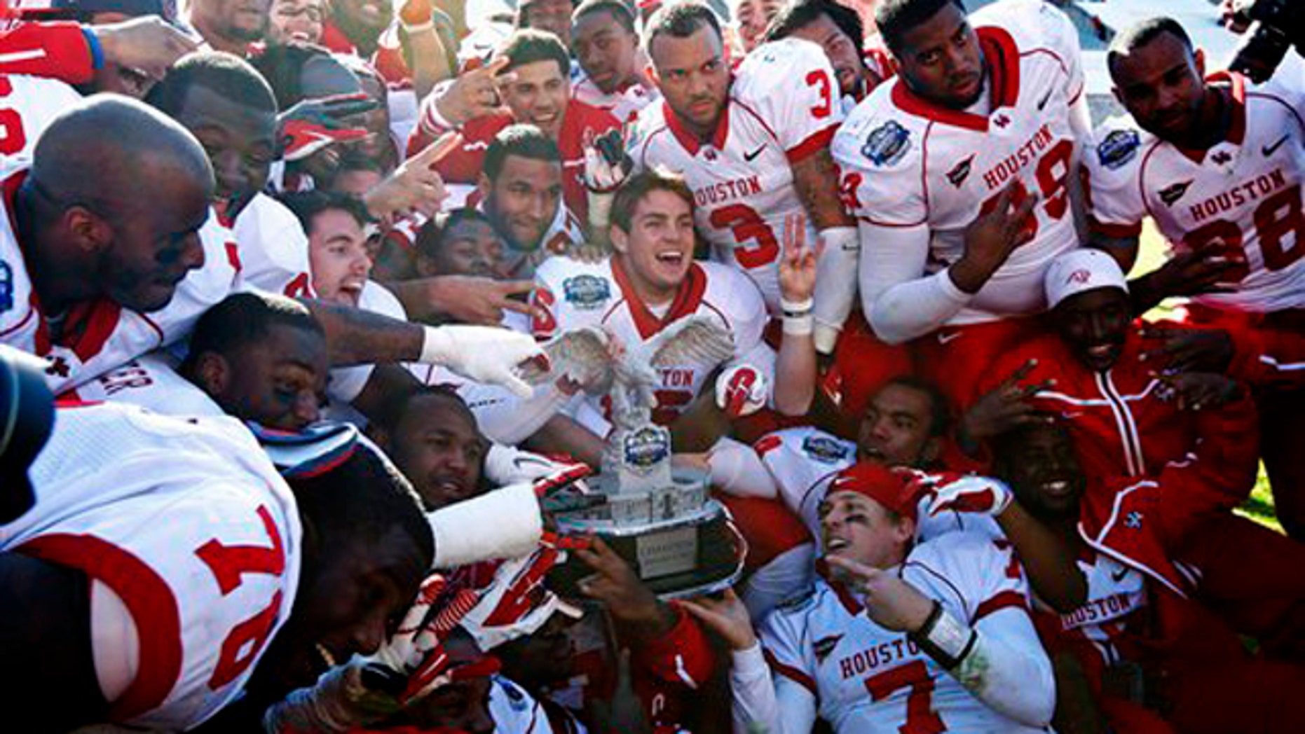Houston players celebrate with the championship trophy after defeating Penn State in the TicketCity Bowl NCAA college football game, Monday, Jan. 2, 2012, at the Cotton Bowl in Dallas.