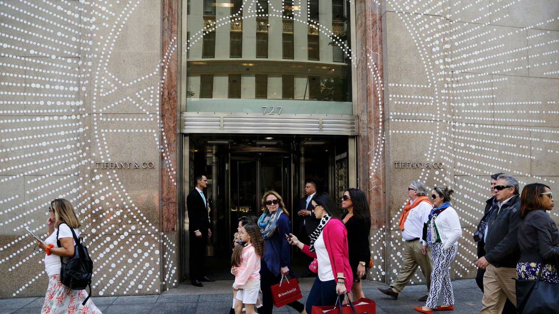 Shoppers walk by Tiffany & Company's Fifth Avenue store in New York.