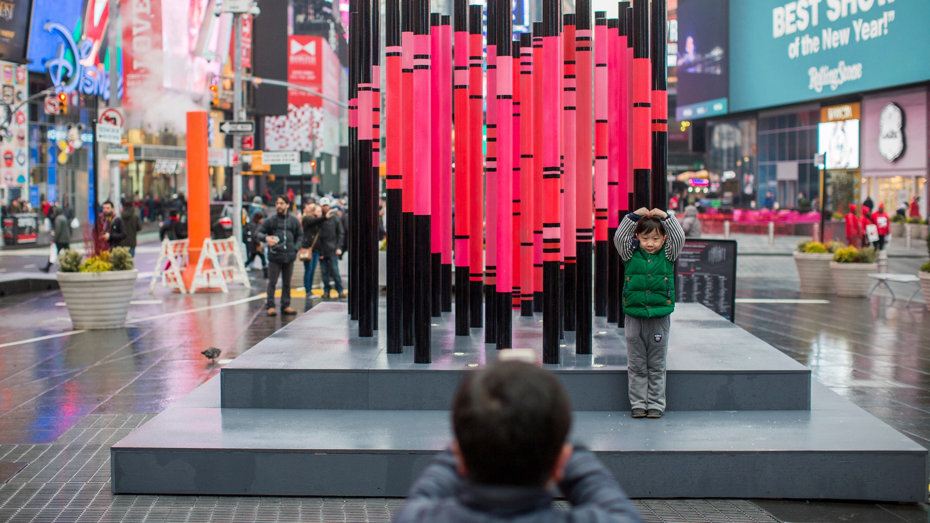 "A visitor to New York's Times Square poses for a photo with the art installation ""We Were Strangers Once Too."""