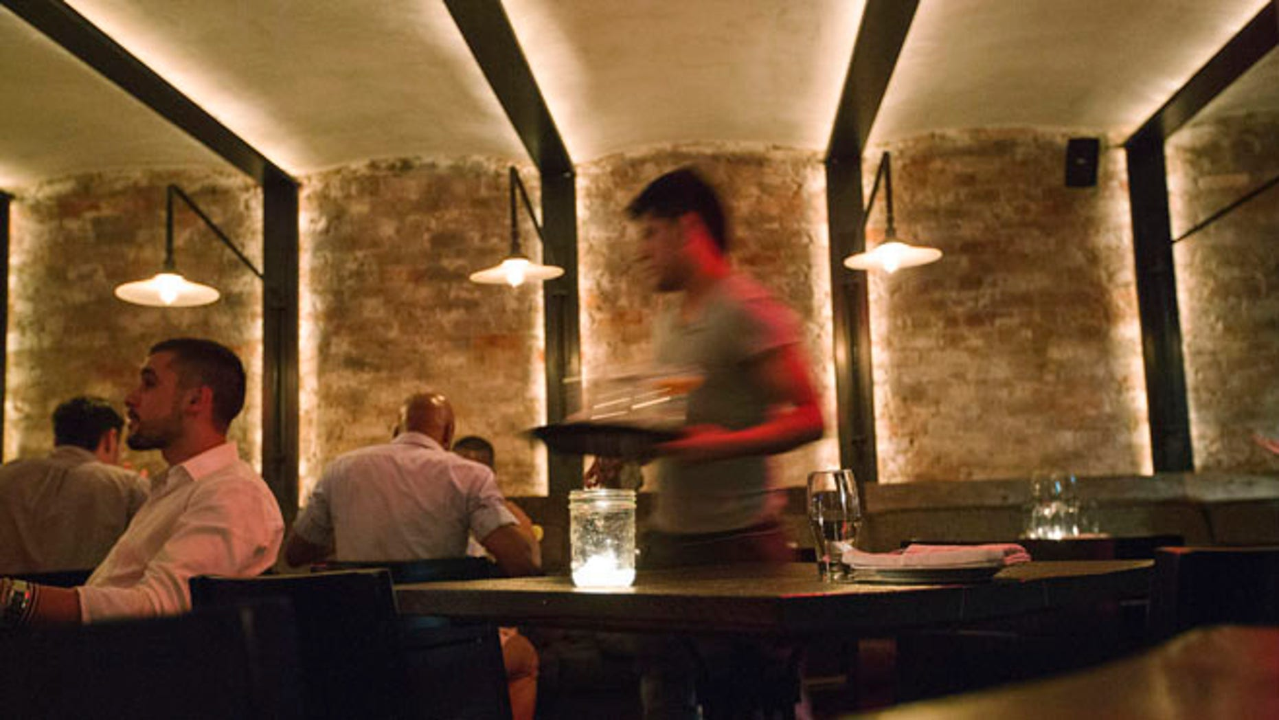 June 12, 2013: A server clears dishes from a table inside a New York restaurant.
