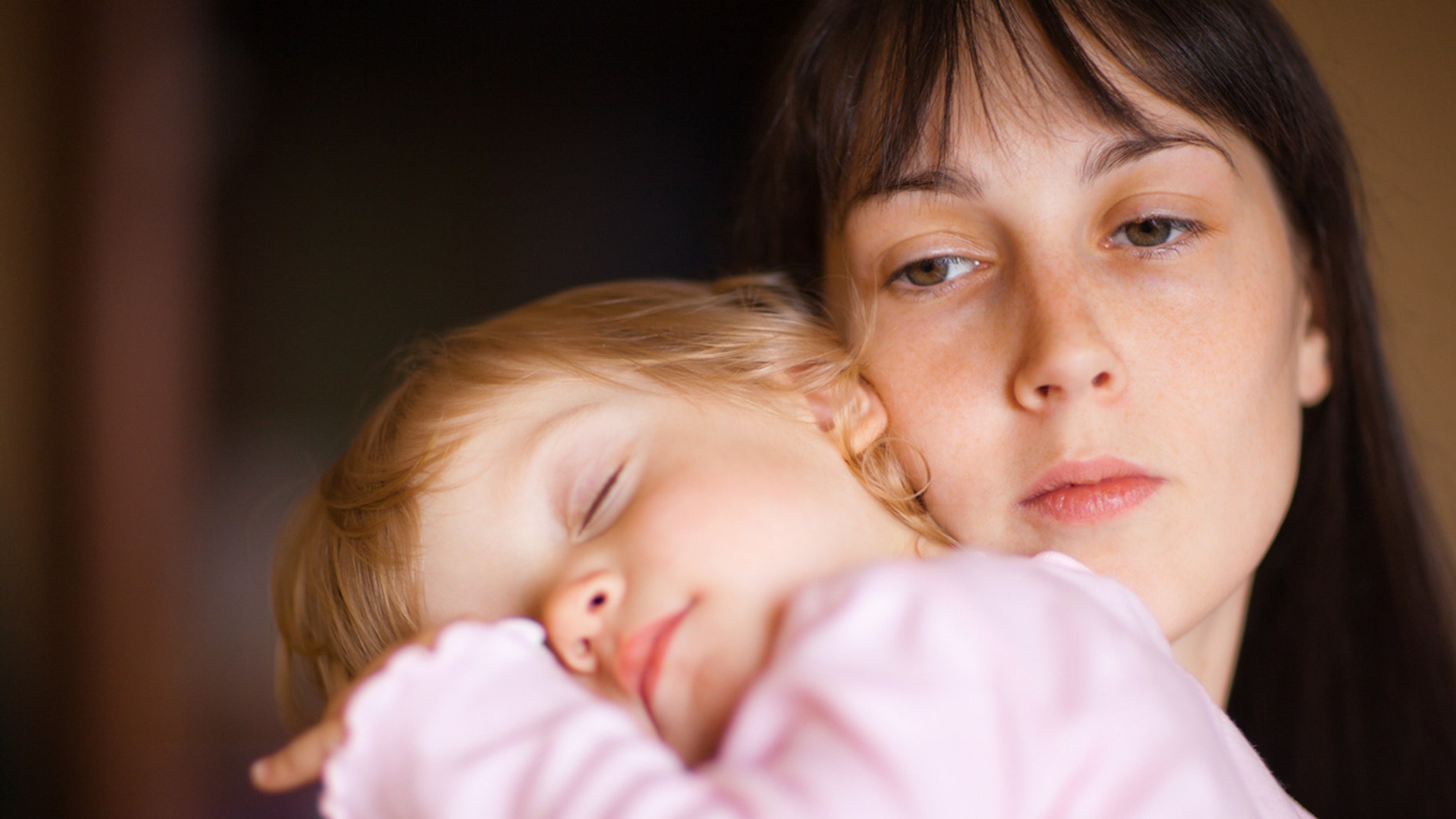 Sleepy little child with mom - shallow DOF, focus on woman's eyes