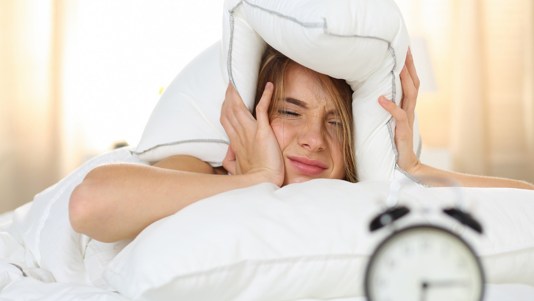 Young beautiful blonde woman lying in bed suffering from alarm clock sound covering head and ears with pillow making unpleasant face. Early wake up, not getting enough sleep, going work concept