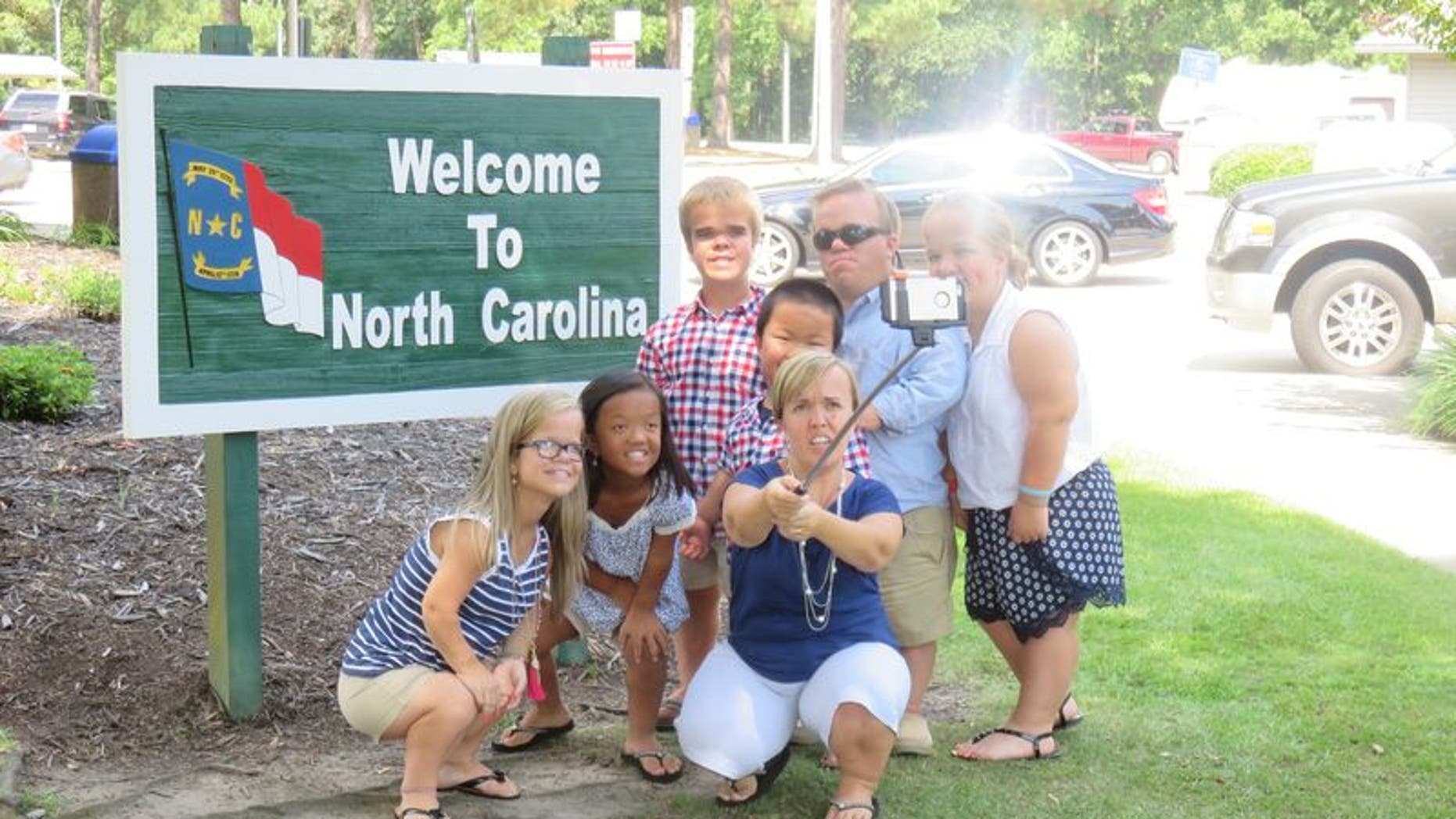 The Johnston family taking a selfie at the North Carolina state border sign.