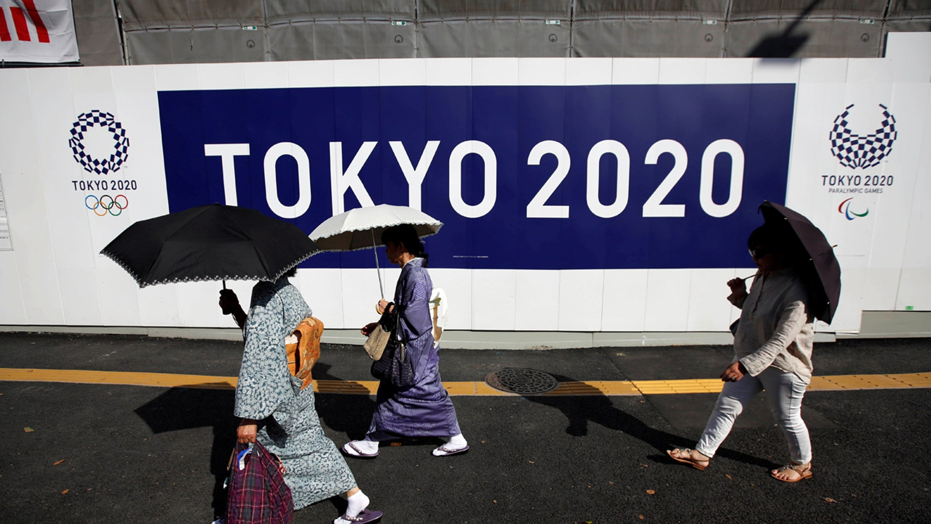 Kimono-clad women walk past at a construction site of a building displaying Tokyo 2020 Olympics and Paralympics emblems in Tokyo, Japan.