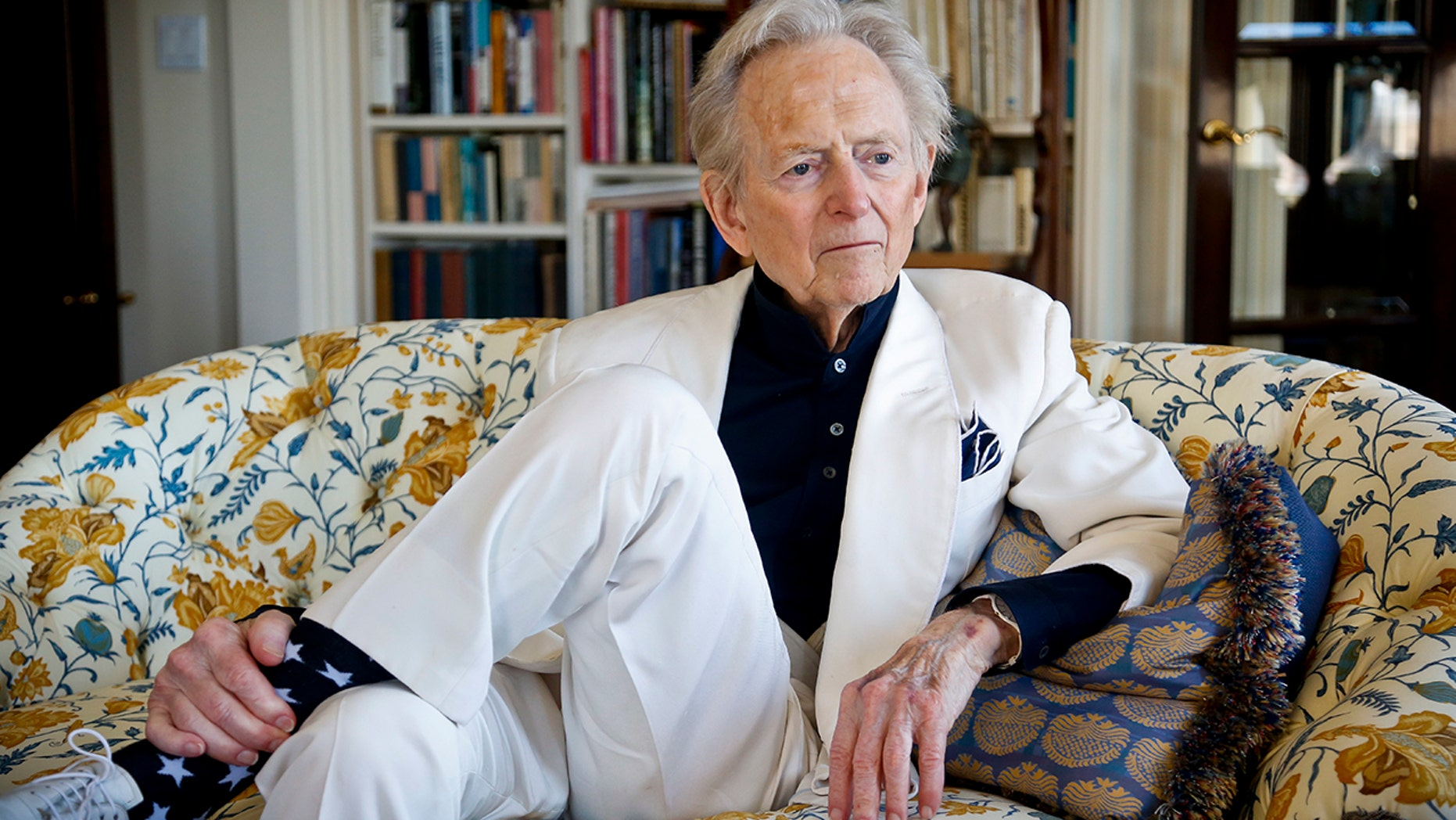 """In this July 26, 2016 file photo, American author and journalist Tom Wolfe, Jr. appears in his living room during an interview about his latest book, """"The Kingdom of Speech,"""" in New York. Wolfe died at a New York City hospital. He was 87."""