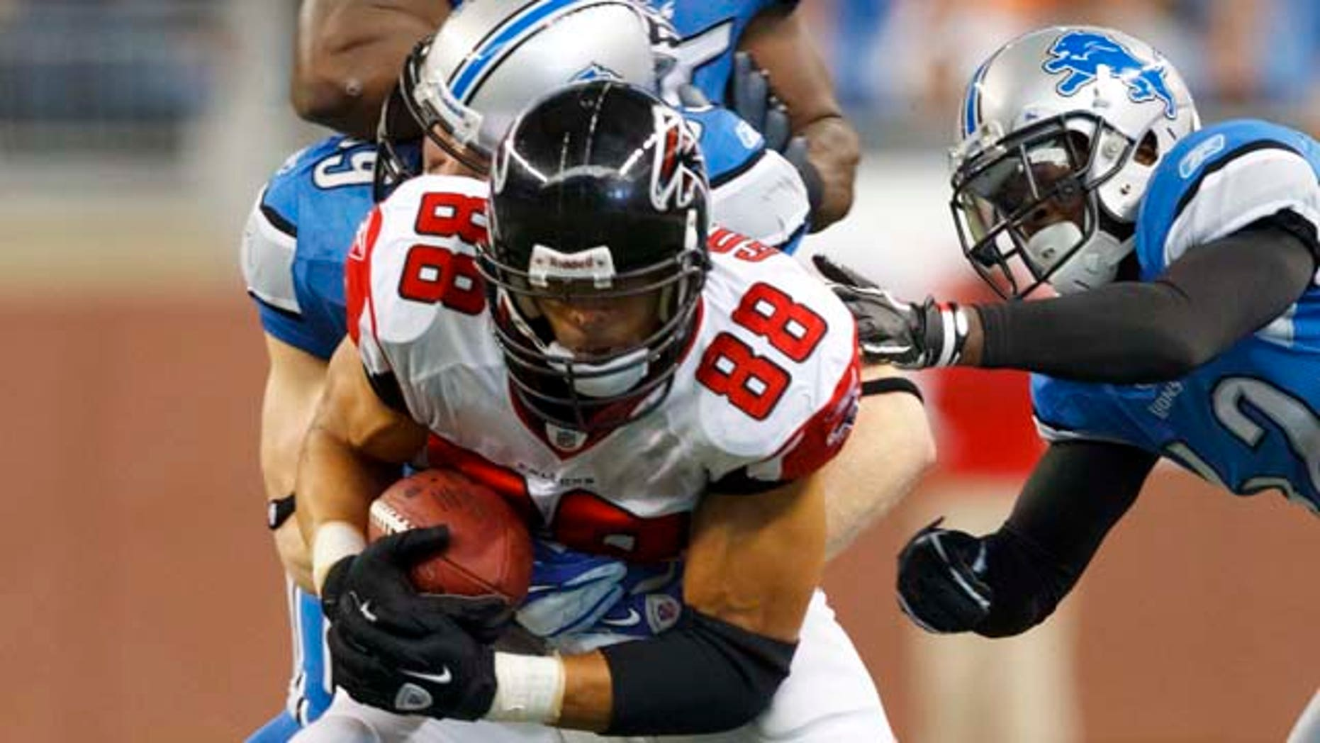 Atlanta Falcons tight end Tony Gonzalez (88) is tackled by Detroit Lions outside linebacker Bobby Carpenter (59), Amari Spievey, right, and linebacker Stephen Tulloch (55) in the third quarter of an NFL football game in Detroit, Sunday, Oct. 23, 2011. Gonzalez had five receptions for 62 yards to pass Marvin Harrison for second place on the NFL career receptions list. (AP Photo/Rick Osentoski)