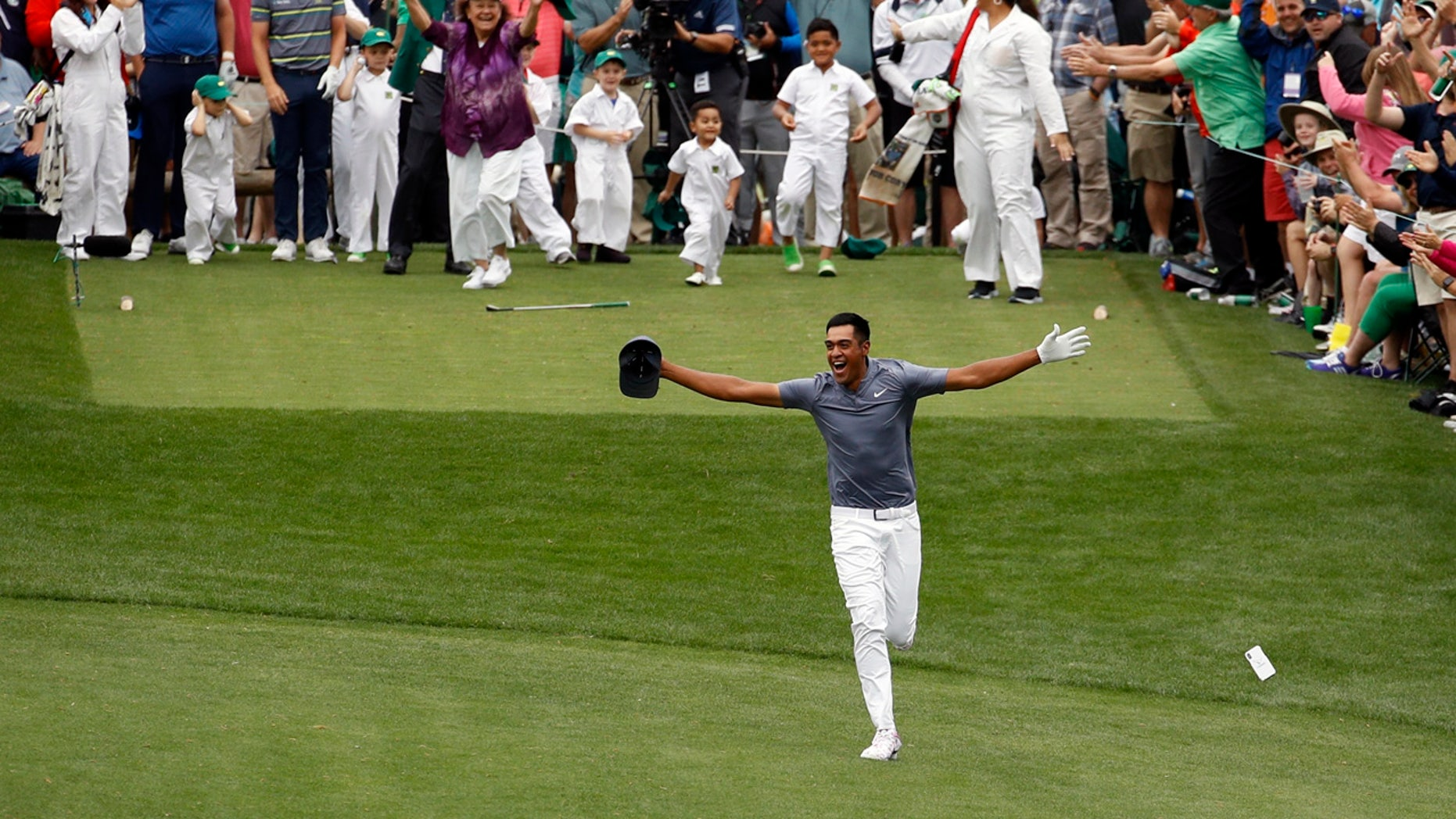 Tony Finau reacts to his hole-in-one at the Masters Par-3 contest seconds before turning his ankle Wednesday.