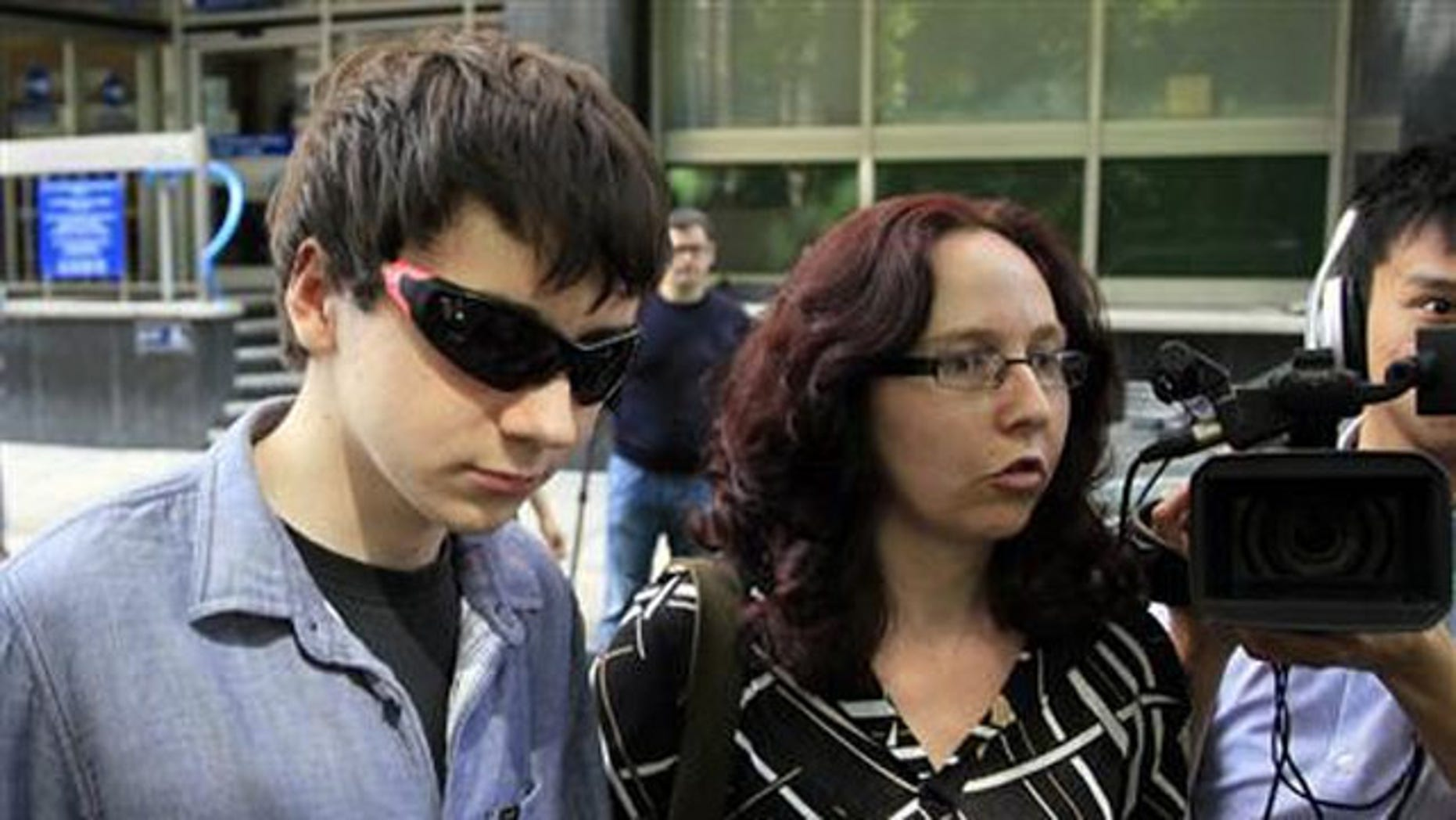 August 1, 2011: Suspected British computer hacker Jake Davis (L) leaves City of Westminster Magistrates' Court in London after being released on bail.