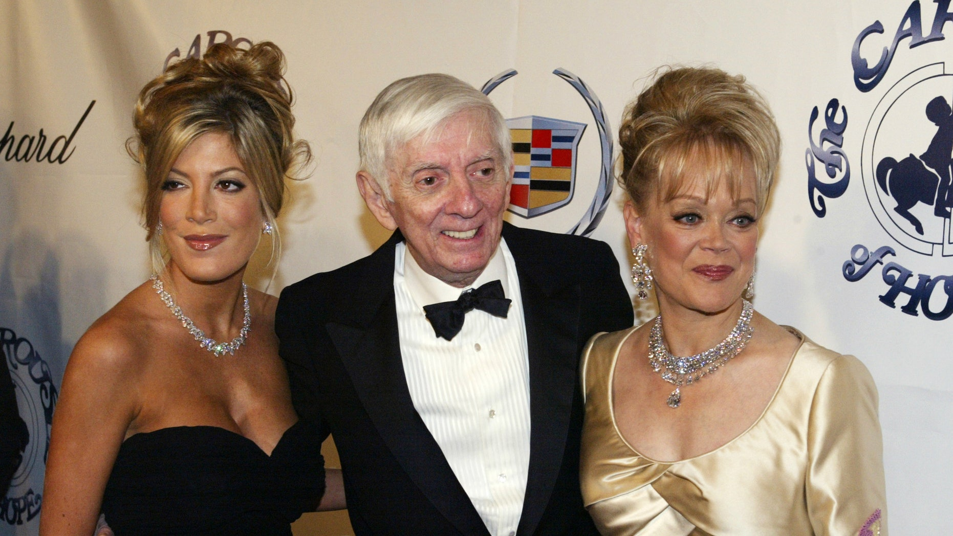 October 15, 2002. Actress Tori Spelling (L) is pictured with her mother Candy Spelling (R) and her late father, television producer Aaron Spelling, at the Carousel of Hope charity ball in Beverly Hills, California.