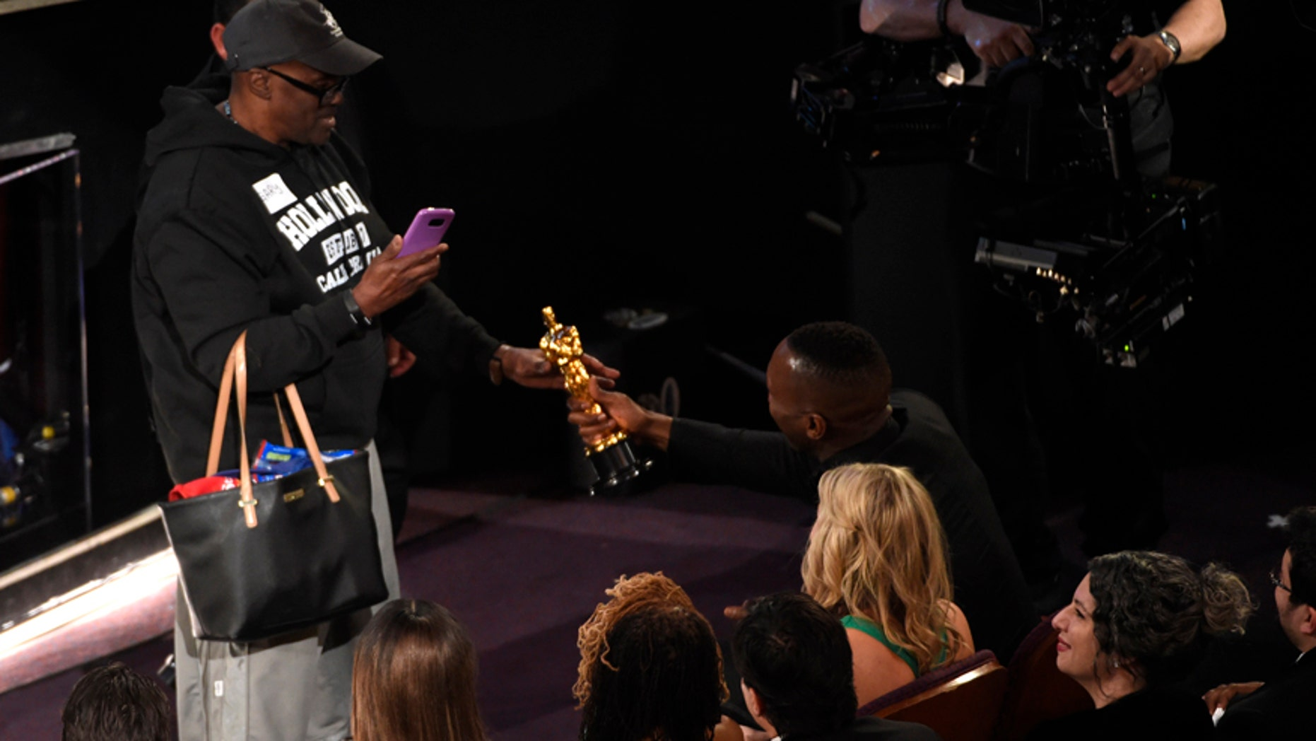 """Mahershala Ali, right, hands his award for best actor in a supporting role for """"Moonlight"""" to a tourist named Gary during the Oscars on Sunday, Feb. 26, 2017, at the Dolby Theatre in Los Angeles."""