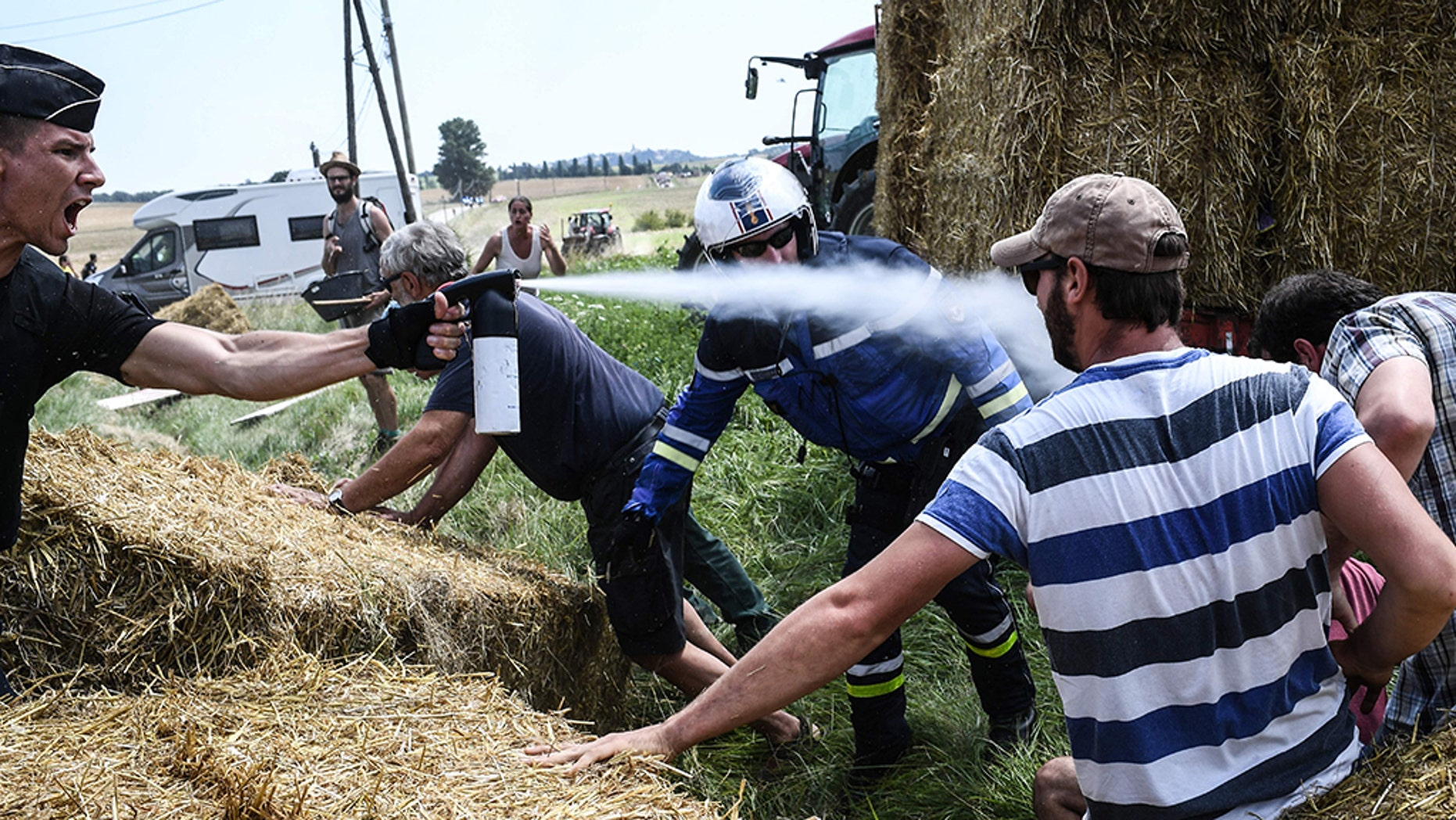 A gendarme, left, sprays tear gas at protesters as other gendarmes remove haystacks from the route of the Tour de France.