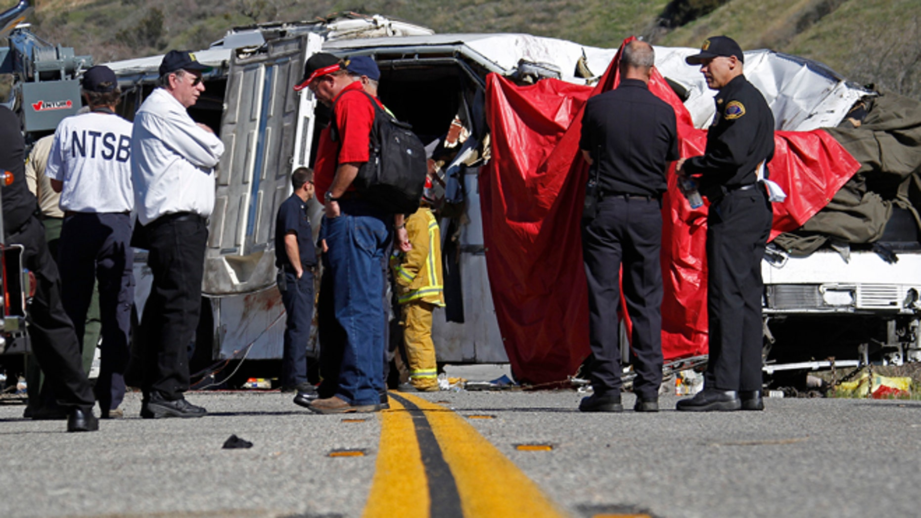Feb. 4: Investigators stand at the scene after a tour bus was lifted back onto the road after it collided with two other vehicles and crashed, killing at least eight people and injuring 38, just north of Yucaipa, Calif.