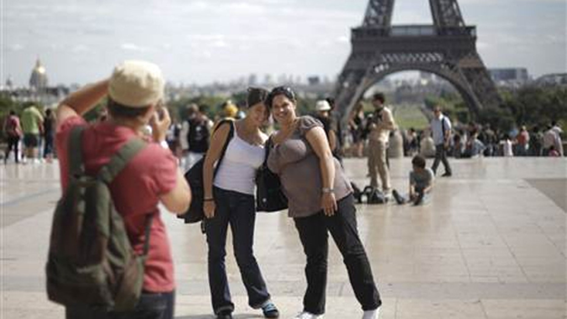 FILE: Tourists pose in front of the Eiffel Tower in Paris.