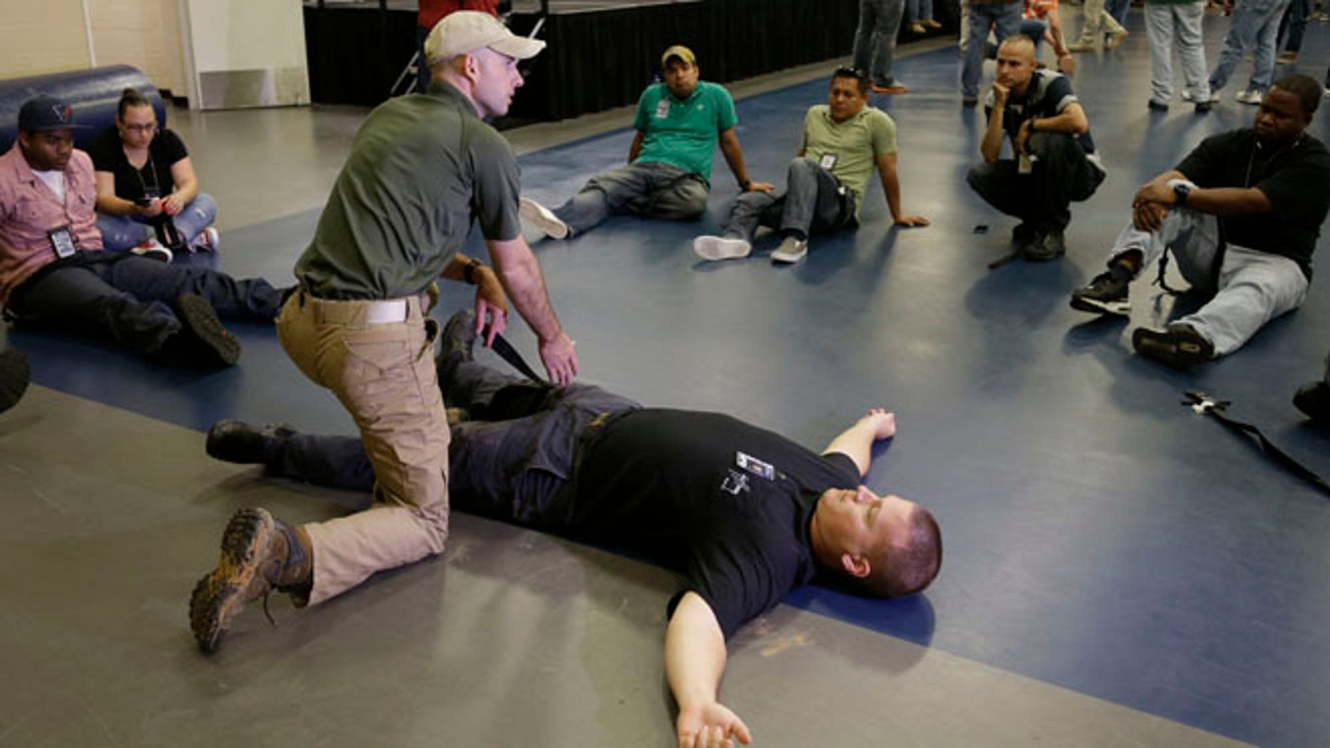 June 3, 2014: Houston police officer Austin Huckabee, left, uses officer Thomas Emmite, Jr, to show other officers how to apply a tourniquet at the police academy in Houston.