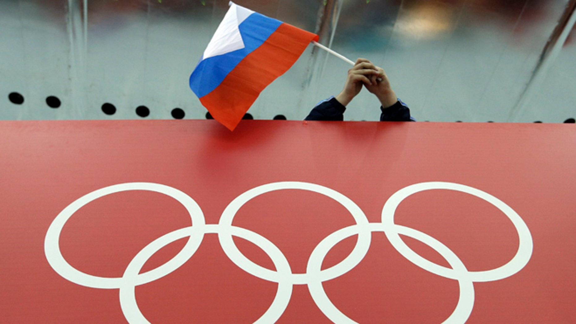 FILE - In this Feb. 18, 2014 file photo, a Russian skating fan holds the country's national flag over the Olympic rings before the start of the men's 10,000-meter speedskating race at Adler Arena Skating Center during the 2014 Winter Olympics in Sochi, Russia. The credibility of the fight against doping in sports will be at stake Friday, June 17, 2016 when track and field's world governing body decides whether to uphold or lift its ban on Russian athletes ahead of the Rio de Janeiro Olympics. Sports geopolitics — and the key issue of individual justice vs. collective punishment — frame the debate heading into the meeting of IAAF leaders in Vienna. (AP Photo/David J. Phillip, file)