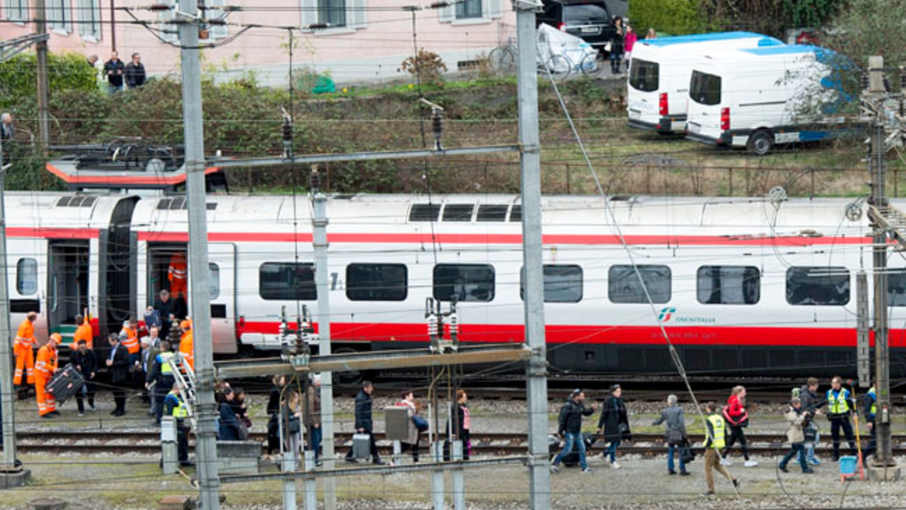 Rescuers help passengers next to a derailed train in the station of Lucerne, Switzerland, Wednesday, March 22, 2017. Swiss police say they are trying to reach people trapped inside the train in the  city of Lucerne, with details of any injuries still unclear. Rail company SBB says the Milan to Basel train derailed Wednesday as it was pulling out of Lucerne's main train station.   (Urs Flueeler/Keystone via AP)