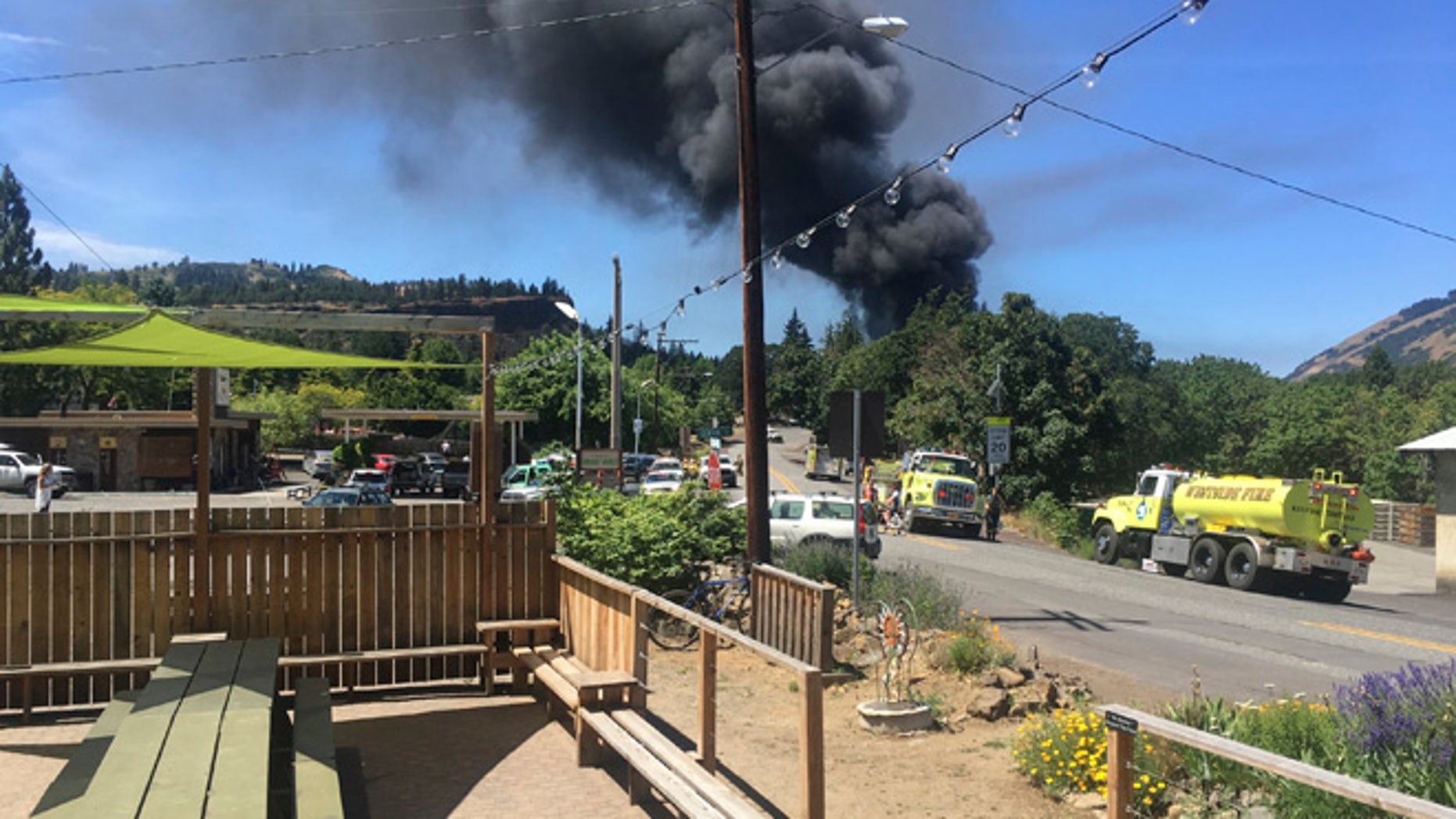 In this photo provided by Silas Bleakley, a train towing cars full of oil sends up a plume of smoke after derailing Friday, June 3, 2016, near Mosier, Ore. The accident happened just after noon about 70 miles east of Portland. It involved eight cars filled with oil, and one was burning. Highway 84 was closed for a 23-mile stretch between The Dalles and Mosier and the radius for evacuations was a half-mile. (Silas Bleakley via AP)