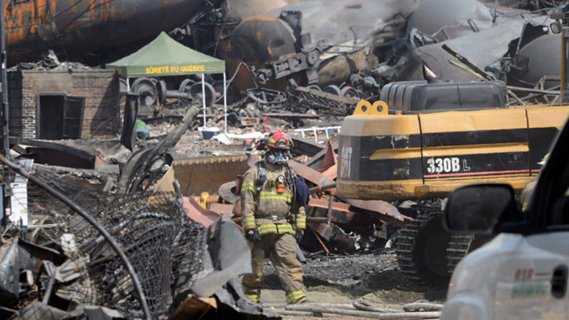 July 6, 2013: This file photo shows a worker, wearing protective gear moving though the wreckage of the oil train derailment and explosion in  in Lac-Megantic, Quebec.