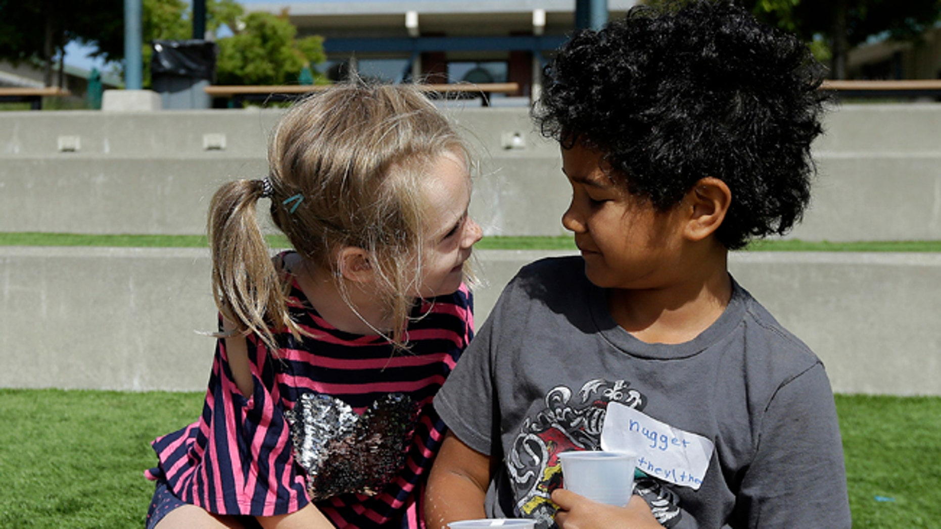 Campers Gracie, left, leans toward Nugget during an activity at the Bay Area Rainbow Day Camp in El Cerrito, Calif., in this July 11, 2017 photo.