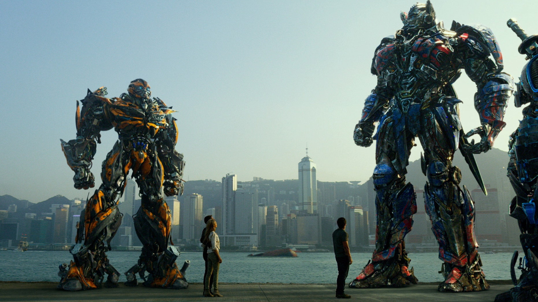 """Hound, Bingbing Li as Su Yueming, Stanley Tucci as Joshua Joyce, Bumblebee, Jack Reynor as Shane Dyson, Nicola Peltz as Tessa Yeager, Mark Wahlberg as Cade Yeager, Optimus Prime, Drift, and Crosshairs, in a scene from the film, """"Transformers: Age of Extinction."""""""