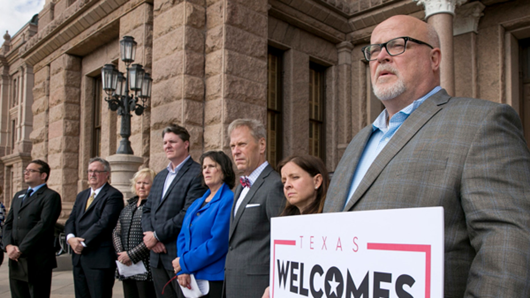 Brad Kent, chief sales and services officer for Visit Dallas, holds a sign at a news conference in Austin, Texas