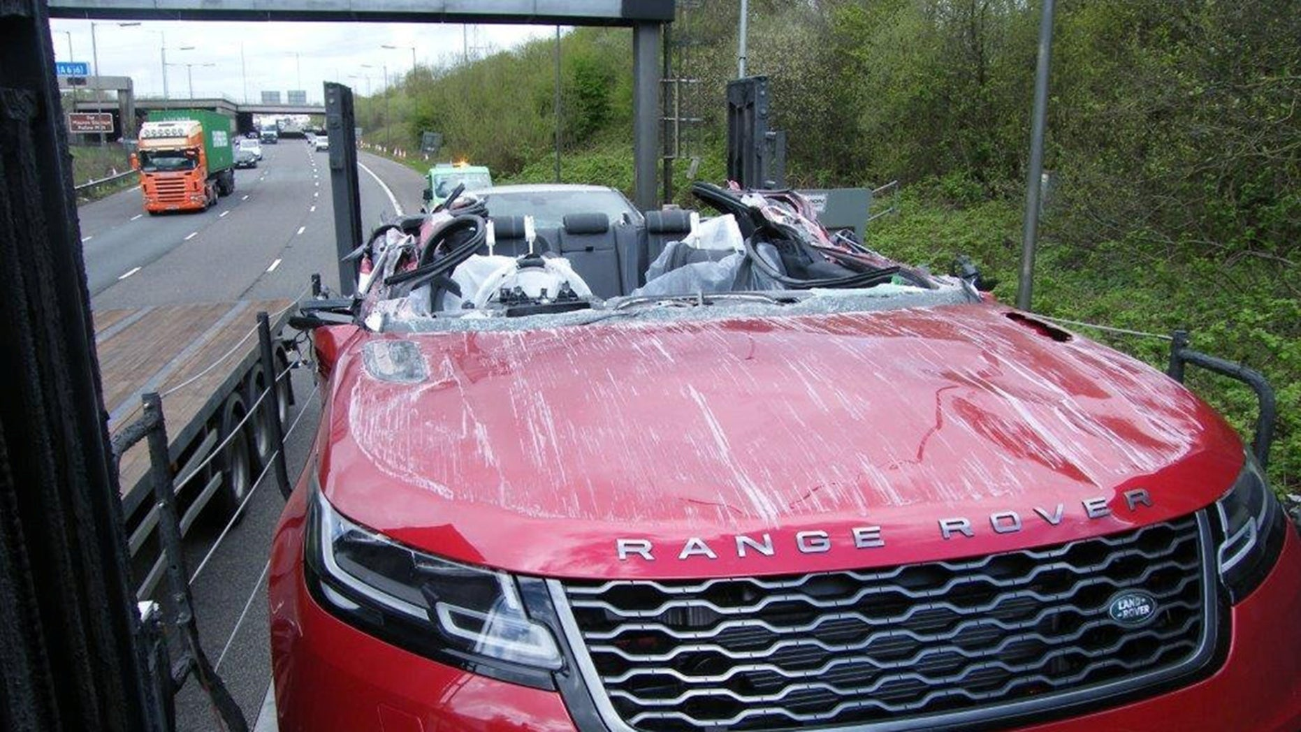 This is what happened when a car transporter collided with a motorway bridge - and accidentally turned a brand new Range Rover into a convertible. See SWNS story SWOOPS; The driver forgot to lower the top deck before travelling along the M61, police said. Fortunately nobody was hurt, but the brand new red car lost its windscreen and windows. But photos show the rest of the car - including the seats, steering wheel and door - remained intact, following the crash near Farnworth, Greater Manchester.