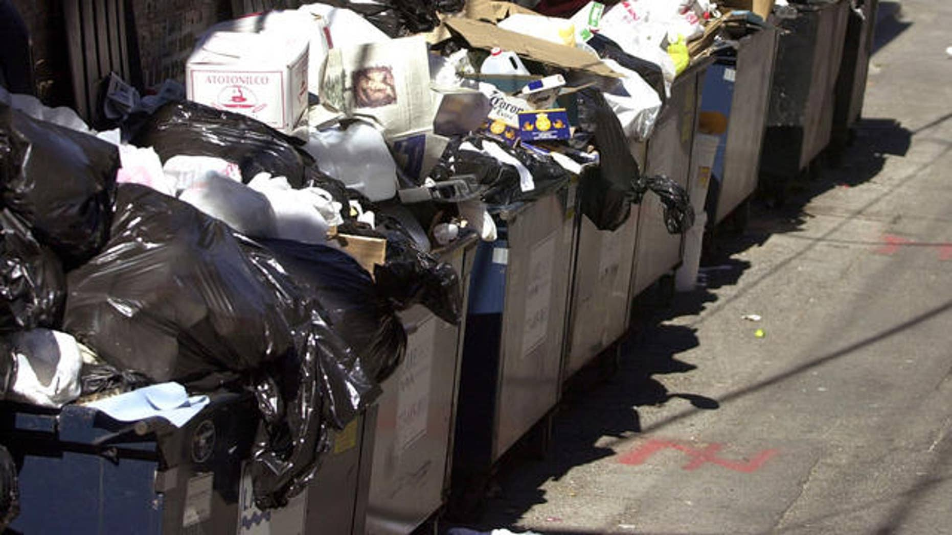 Trash overflows from dumpsters behind an apartment building. (AP)