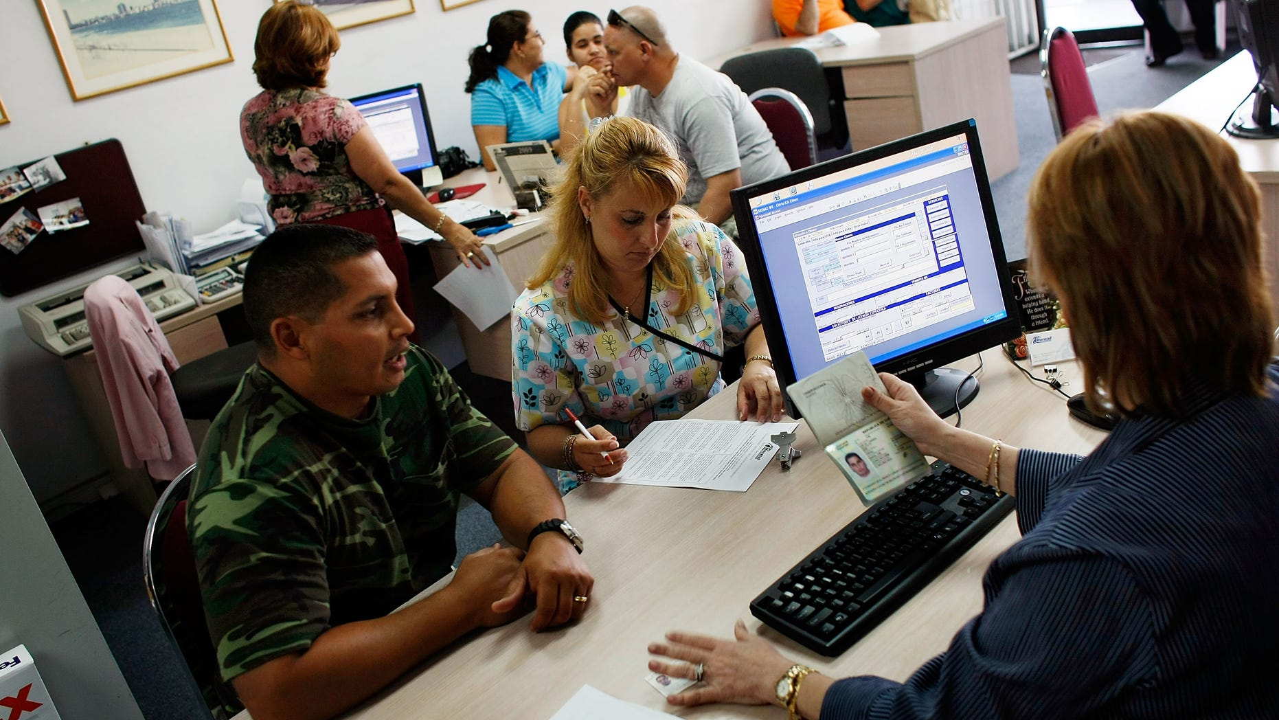 MIAMI - APRIL 13:  Omar Garcia (L) and Giselle Bordin purchase tickets to Cuba from travel agent Marizela Somosa in the offices of Marazul Charters on April 13, 2009 in Miami, Florida. Today, U.S. President Barack Obama  loosened travel restrictions for Cuban Americans traveling to Cuba as well as money transfers to the island.  (Photo by Joe Raedle/Getty Images)