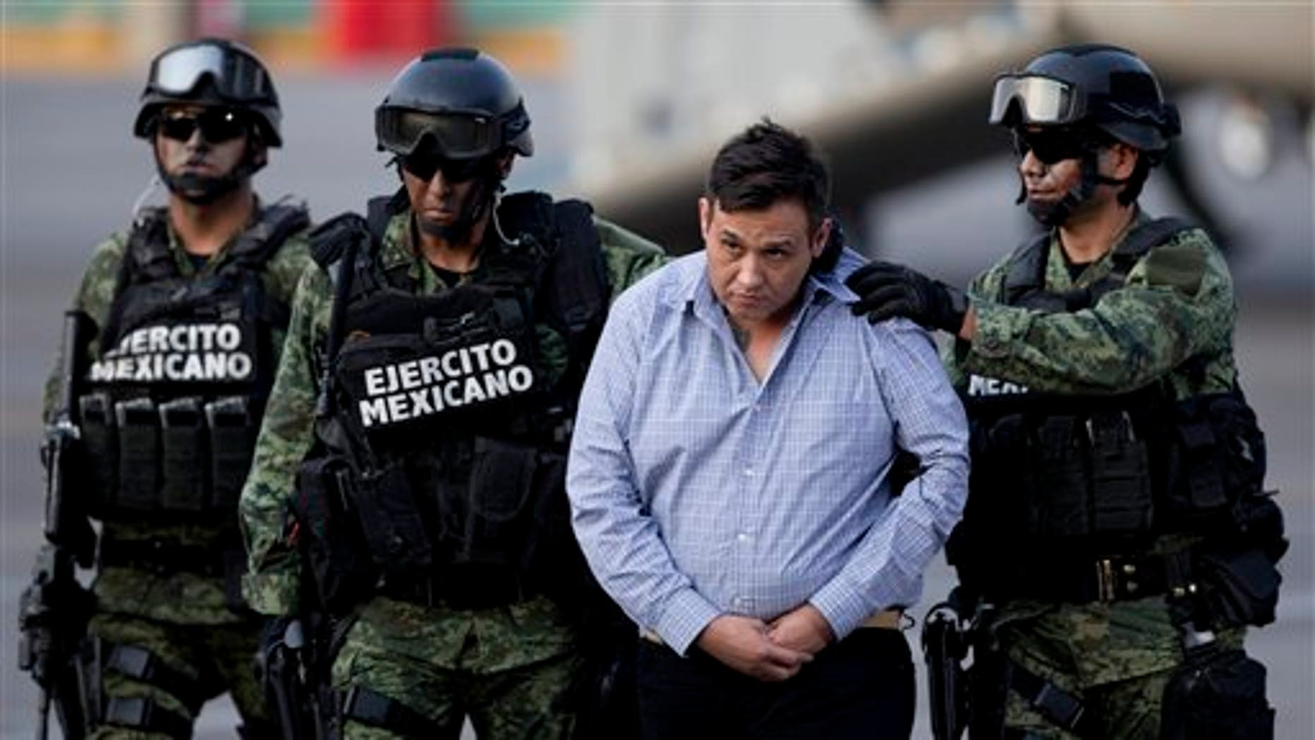 """Soldiers escort a man who authorities identified as Omar Trevino Morales, alias """"Z-42,"""" leader of the Zetas drug cartel, as he is moved from a military plane to a military vehicle at the Attorney General's Office hangar in Mexico City, Wednesday, March 4, 2015. An official who was not authorized to be quoted by name because of government policy, said Morales was arrested on Wednesday in a pre-dawn raid in San Pedro Garza Garcia, a wealthy suburb of the northern city of Monterrey. (AP Photo/Eduardo Verdugo)"""