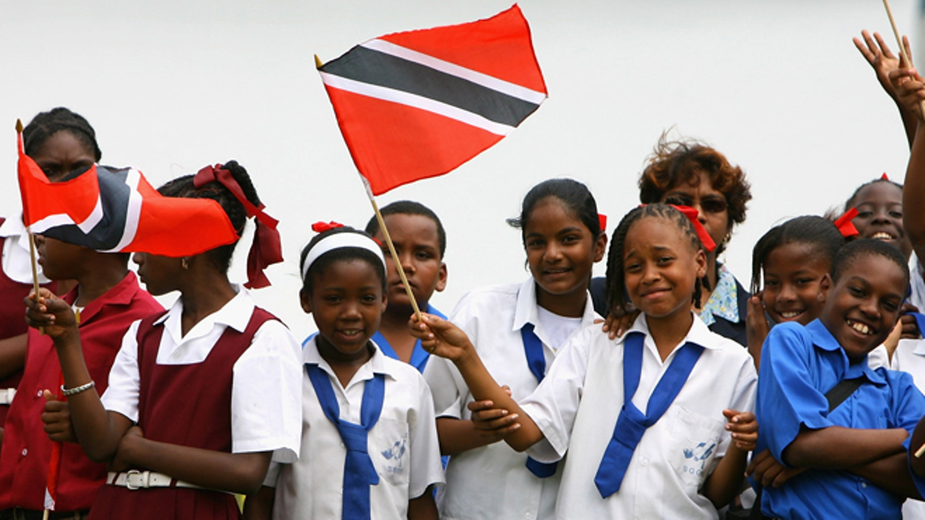 PORT OF SPAIN, TRINIDAD AND TOBAGO - MARCH 05:  Children wave flags at Queen's Cricket ground on the second day of a three day tour of Trinidad and Tobago on March 5, 2008 near Port of Spain, Trinidad. The Royal Couple have arrived in Trinidad on the first leg of a ten day tour of the Caribbean. Sir Donald Gosling's Yacht Leander will transport the couple from Island to Island, then to their final destination, Jamaica.  (Photo by Chris Jackson/Getty Images)