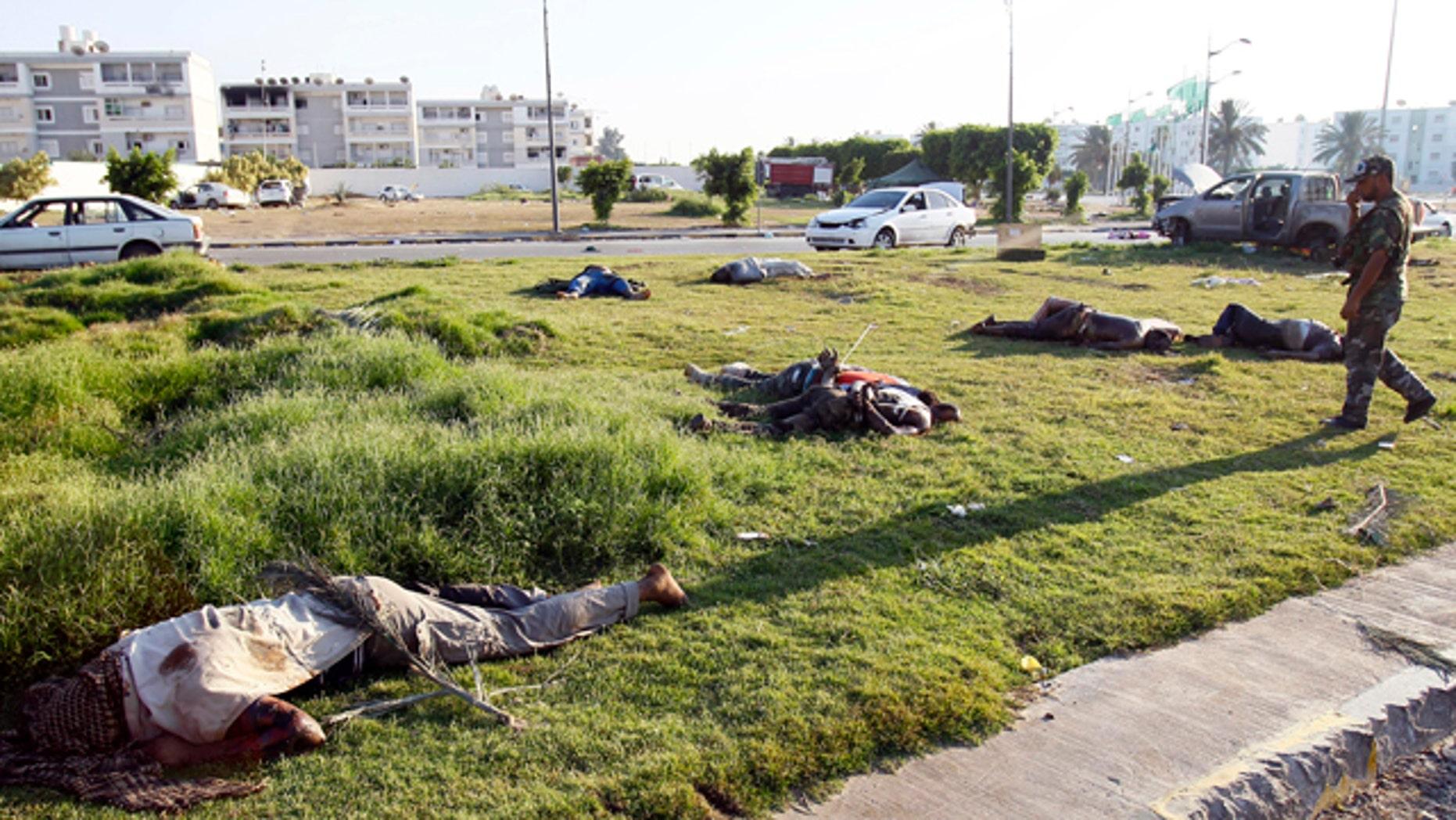 Aug. 25: Libyan rebel walks by dead bodies in Abu Salim district in Tripoli, Libya.