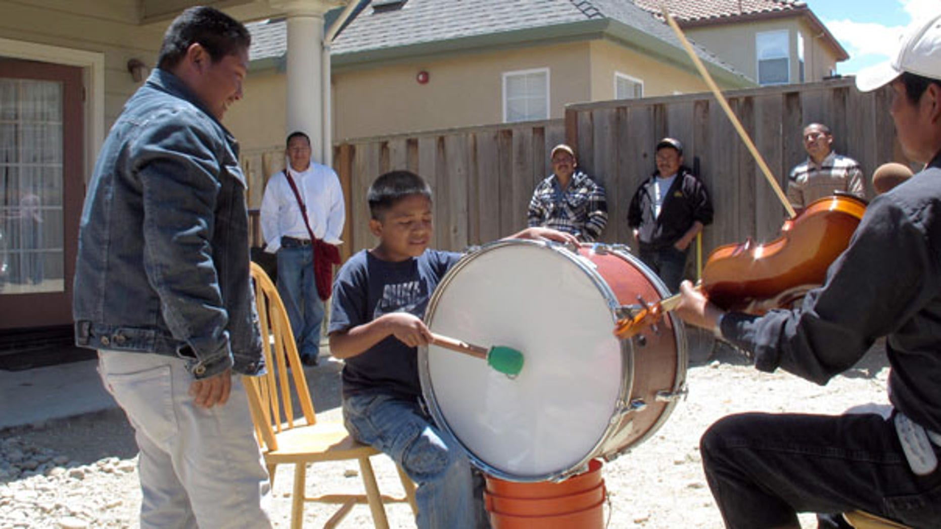 n this May 30, 2011 photo, Trique Indian children, whose families migrated from the Mexican state of Oaxaca, learn how to play traditional instruments at a community get-together in Greenfield, Calif. (AP Photo/Gosia Wozniacka)