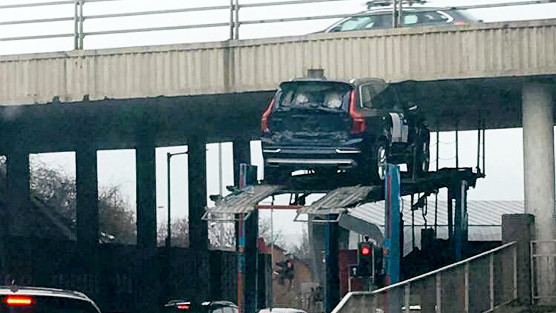 """This picture shows the moment a car got stuck under a bridge while on top of a transporter.  See CENTRE PRESS story CPCAR.  Kirsty Adams was driving from her granddad's funeral at around 3pm on Thursday until she witnessed """"a Volvo"""" trapped underneath the bridge.  According to the 33-year-old, another car fell to the ground as the transporter attempted to drive under the low bridge.  The incident which happened near a roundabout at the Hillington Industrial Estate in Glasgow left the mother-of-one and her partner stunned."""