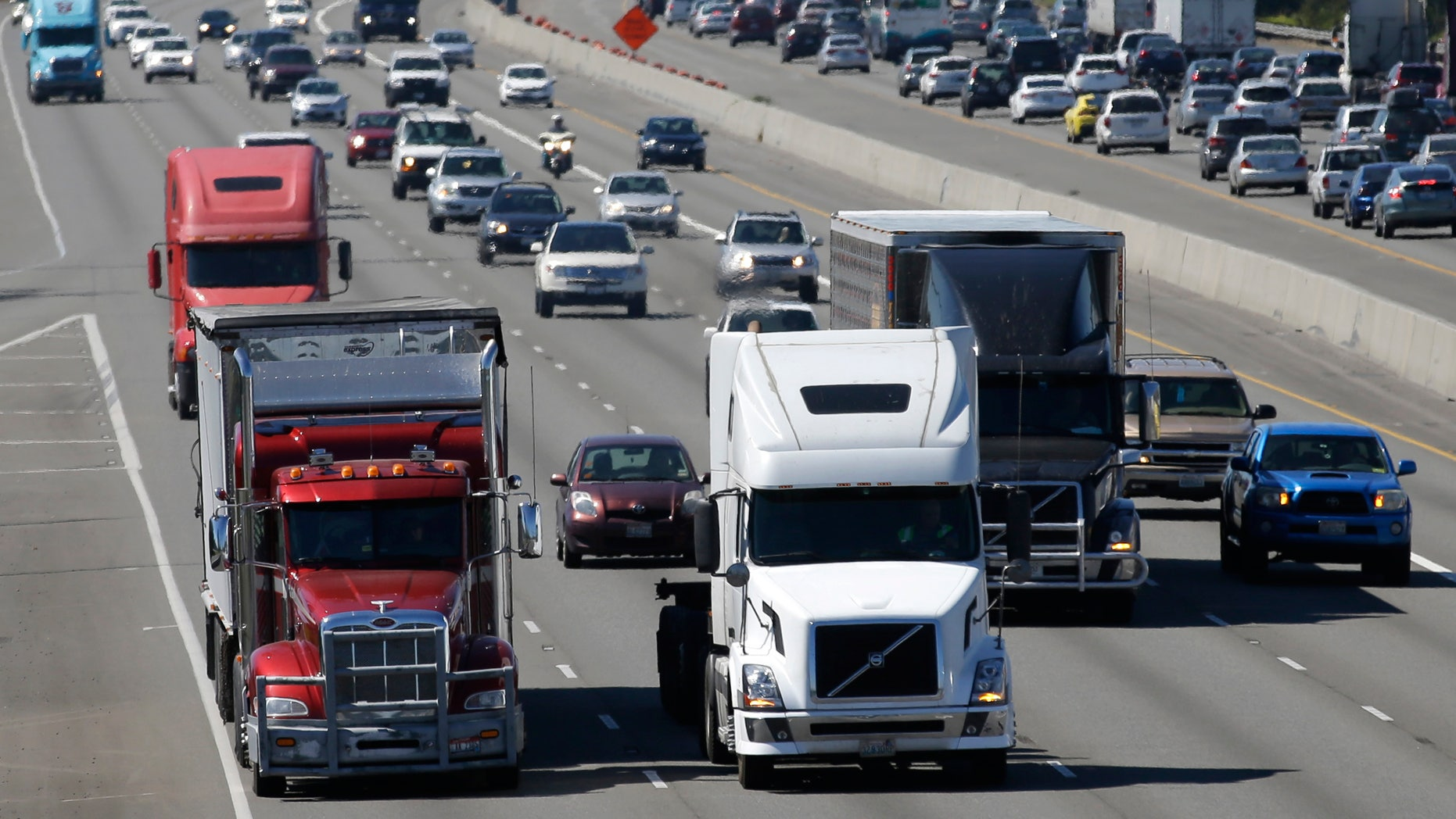 FILE - In this Wednesday, Aug. 24, 2016, file photo, truck and automobile traffic mix on Interstate 5, headed north through Fife, Wash., near the Port of Tacoma. (AP Photo/Ted S. Warren, File)